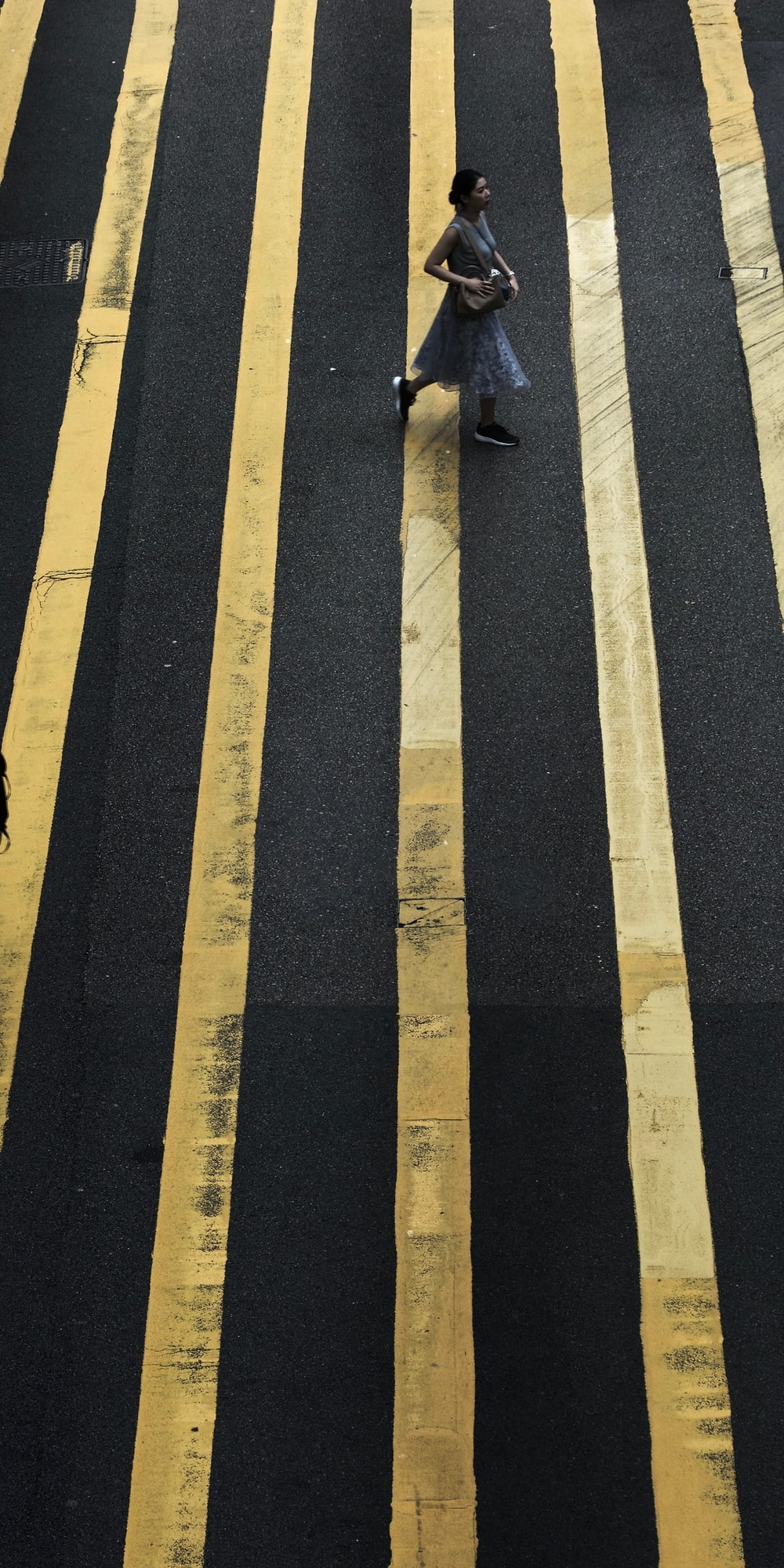 woman crossing pedestrian during daytime
