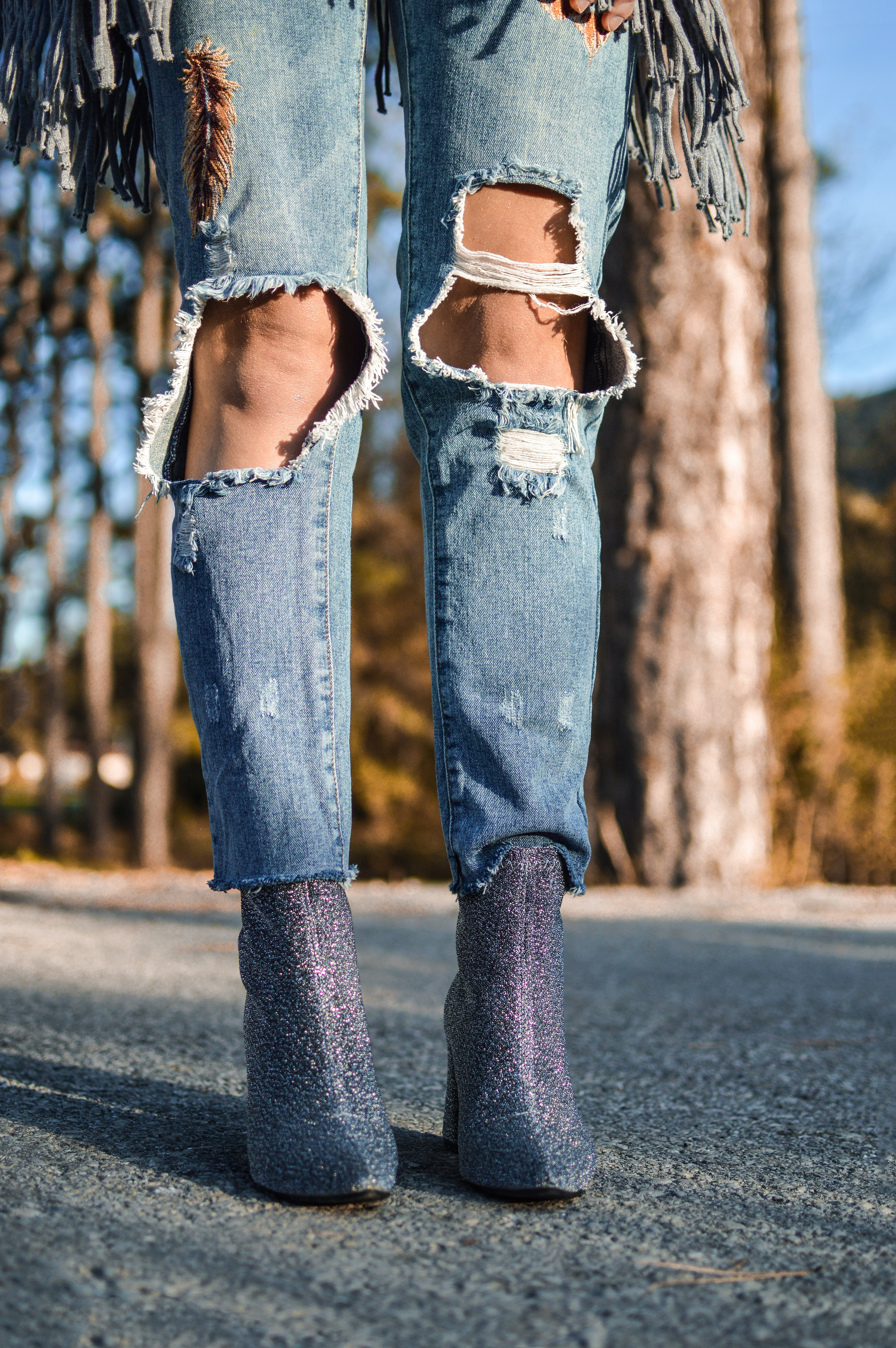 woman wearing distressed blue denim jeans and pair of purple glitter booties