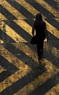 woman with shoulder walking on pedestrian lane