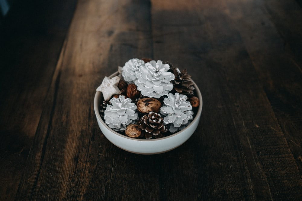 silver and black pinecone decor in white bowl on table