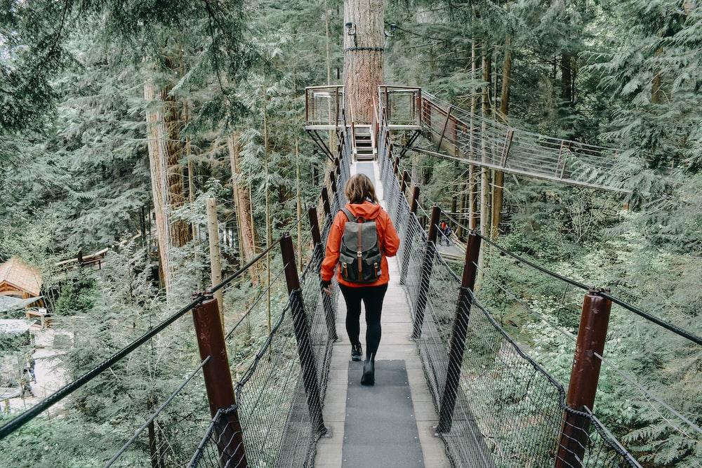 woman walking on black bridge