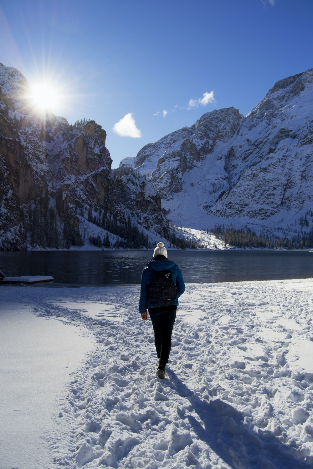 person walking on snow near body of water and mountains