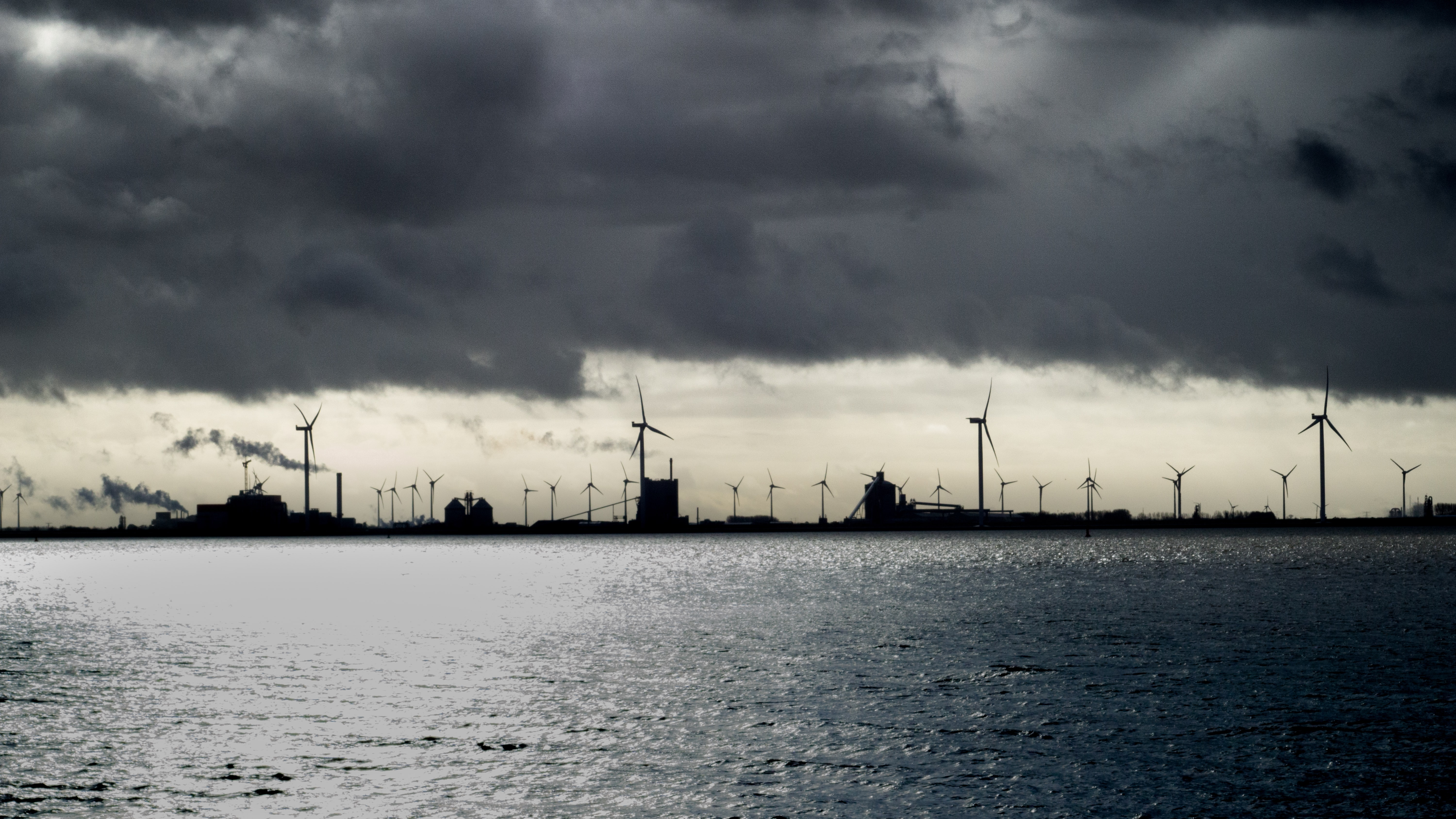 silhouette of wind turbines under cloudy sky