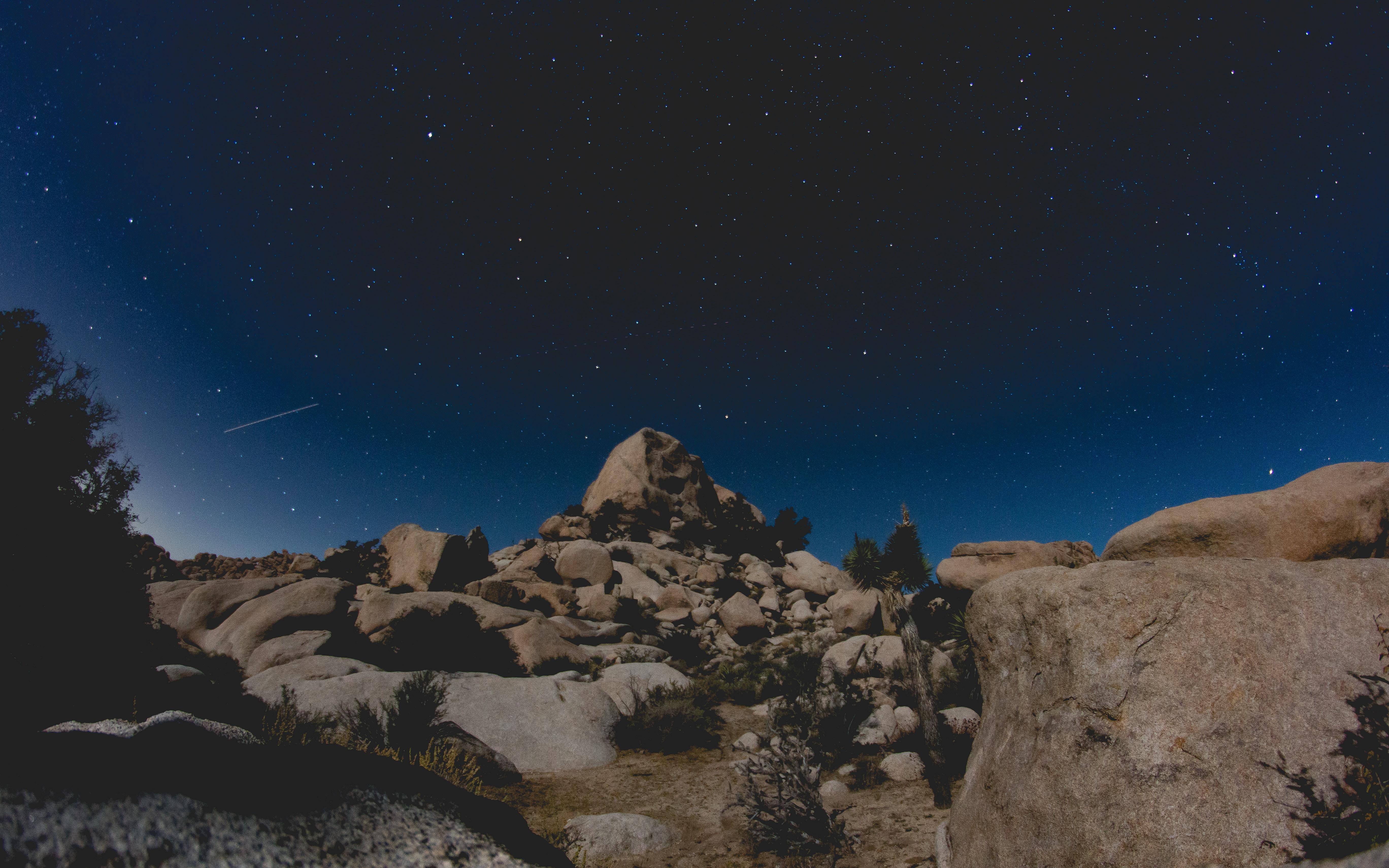brown rock formation under blue night sky