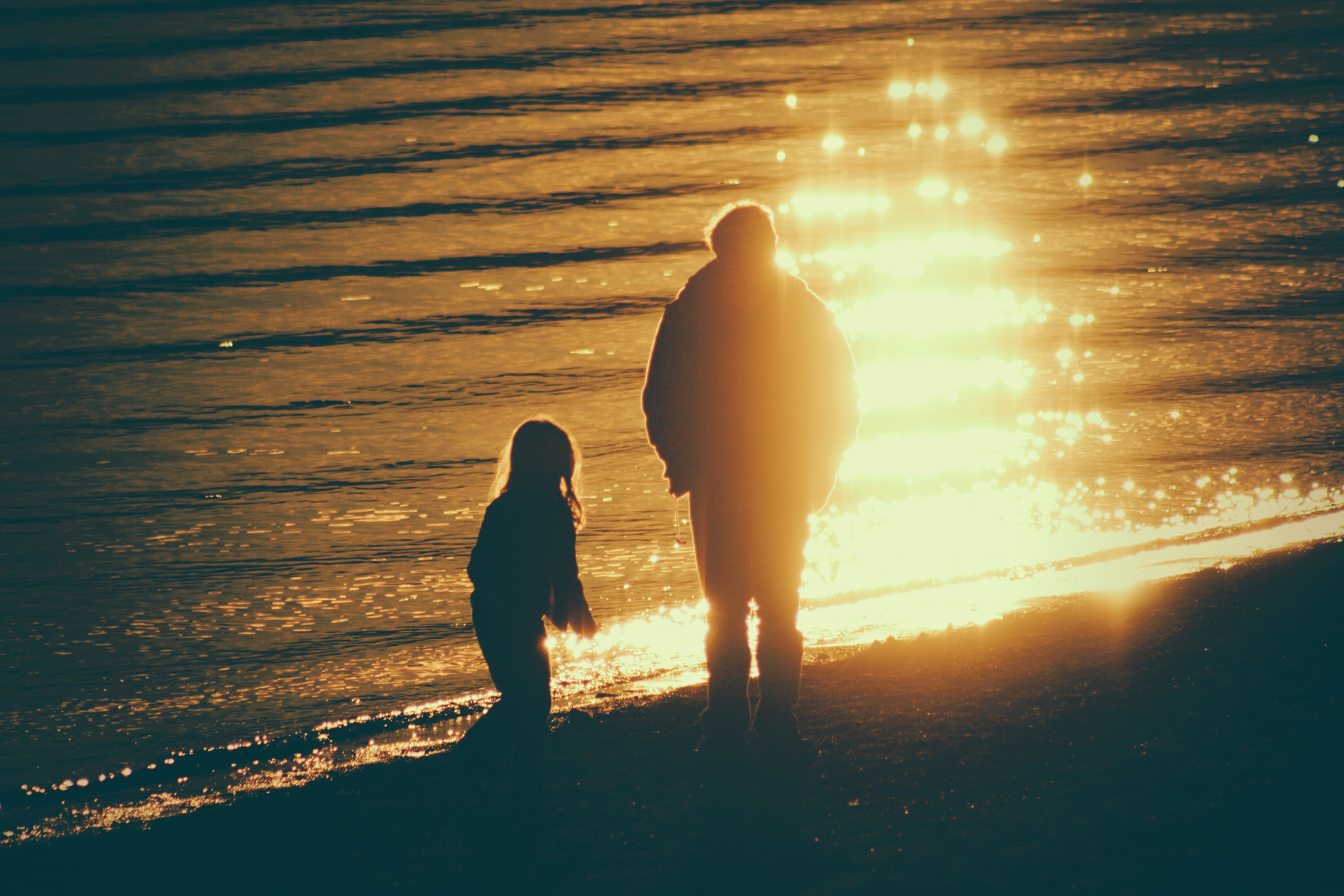 adult and child near seashore during sunset