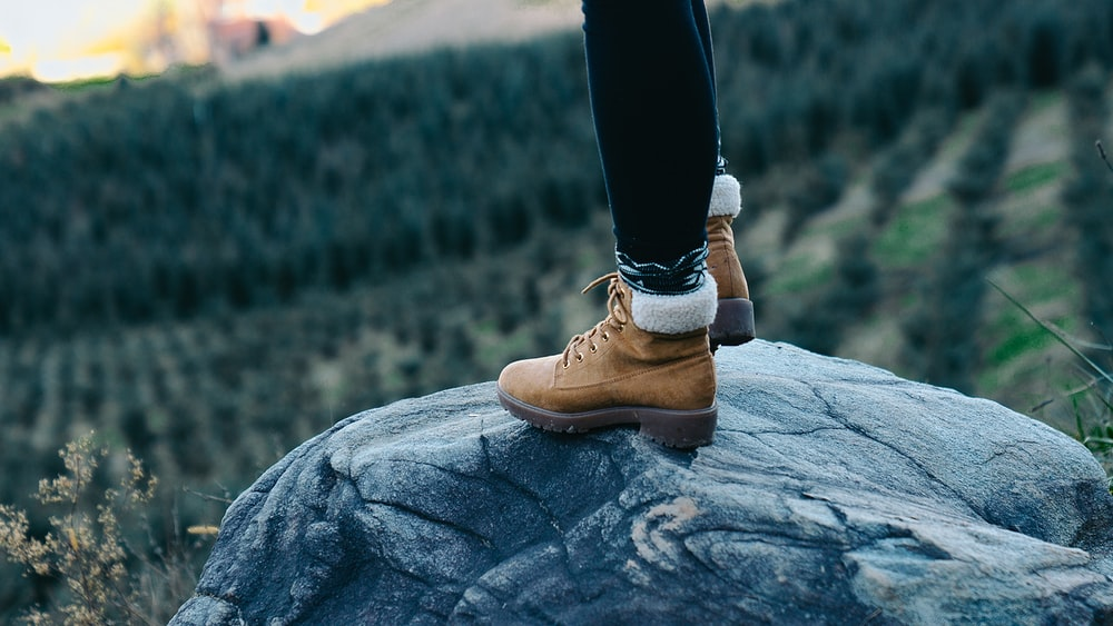 selective focus photography of person standing on rock