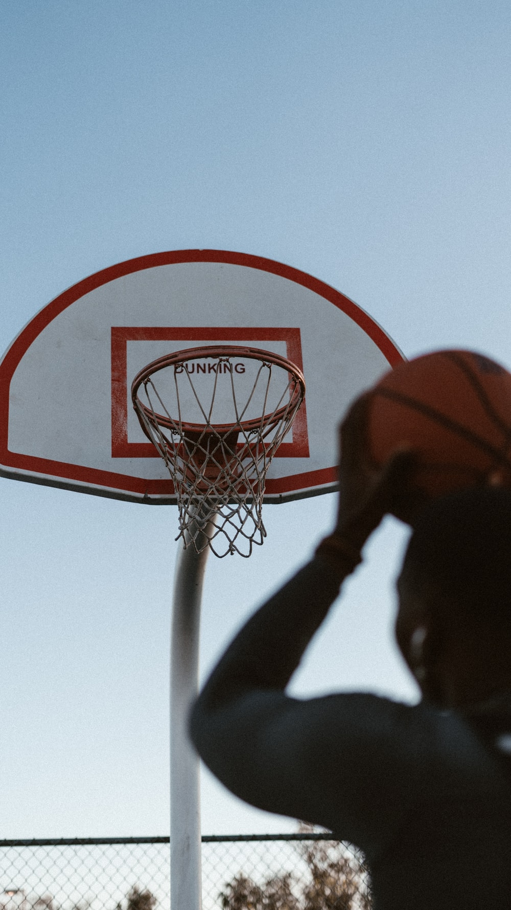 person trying to shoot the ball near basketball hoop