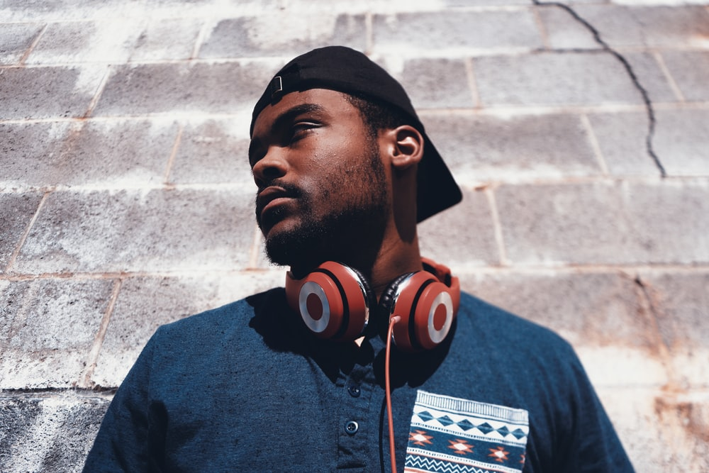 man in blue top standing beside wall