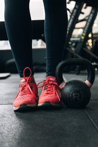 person standing beside kettle bell