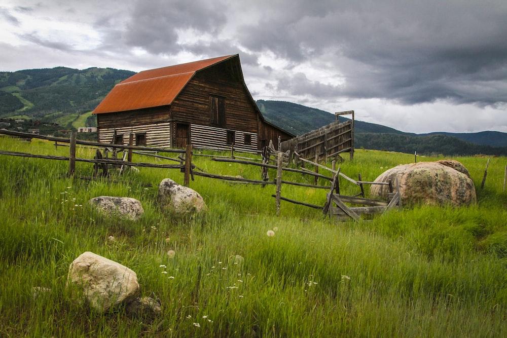 brown wooden barn in high ground at daytime