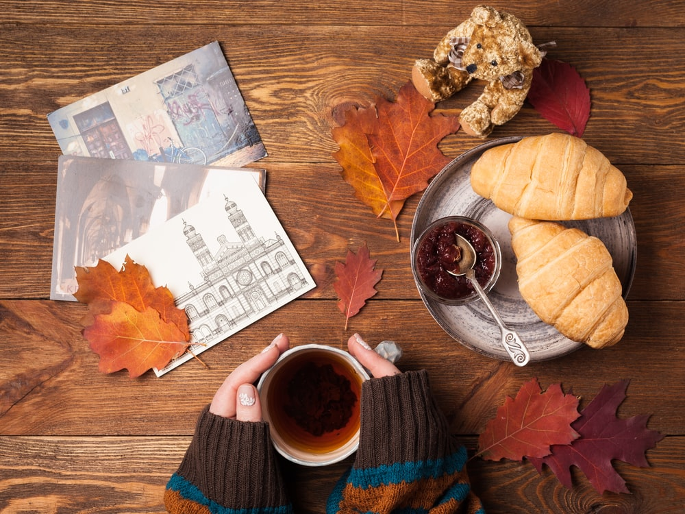 flat lay photography of person holding teacup with two croissant bread on gray tray