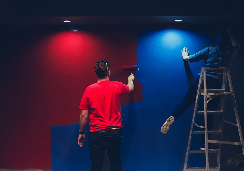 man and woman painting wall
