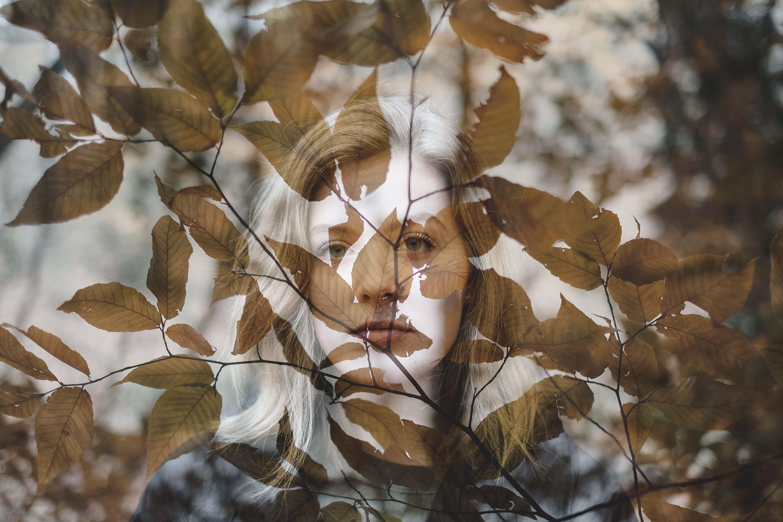 woman behind brown leaves