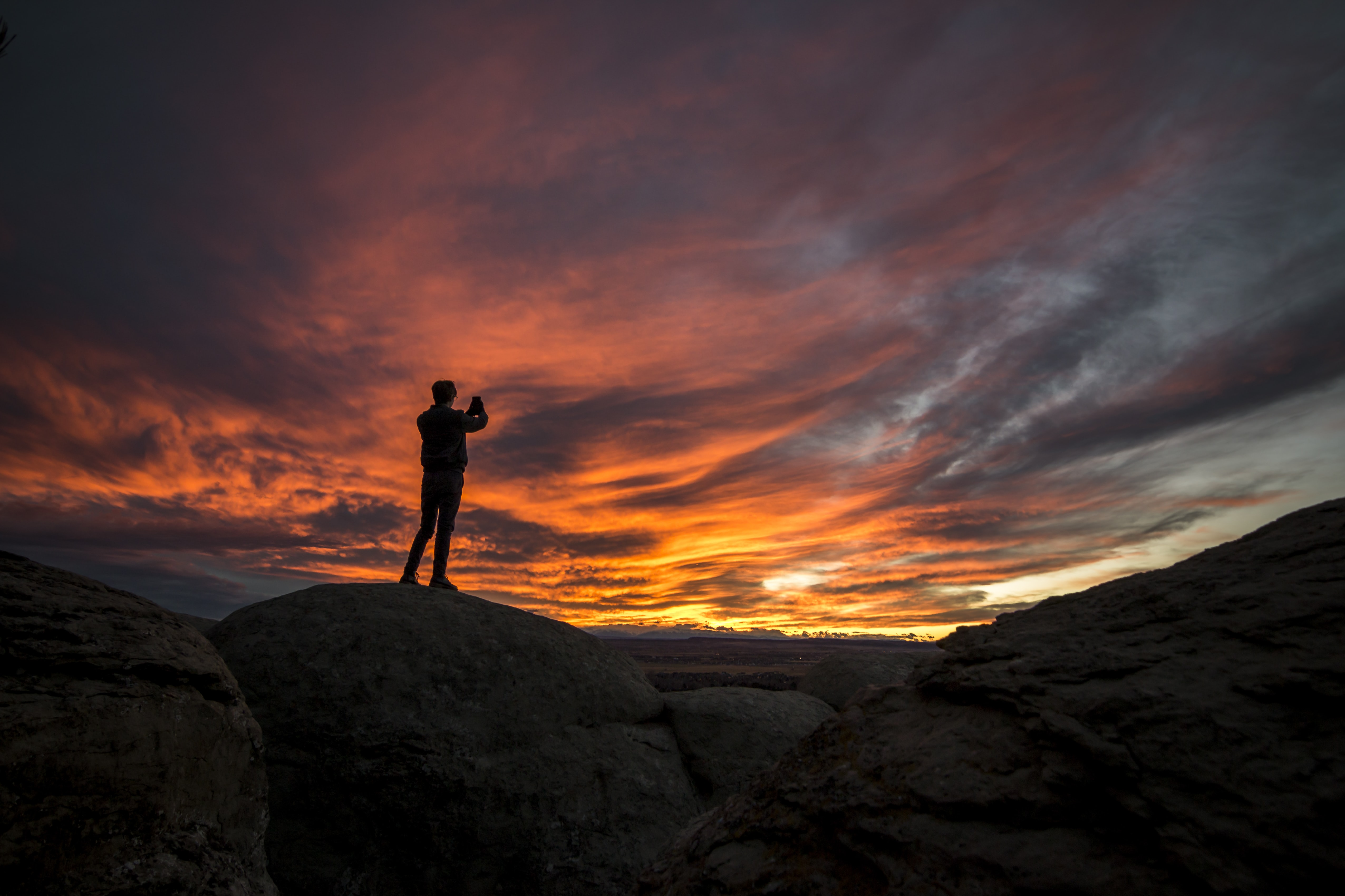 man standing on rocks under cloudy sky