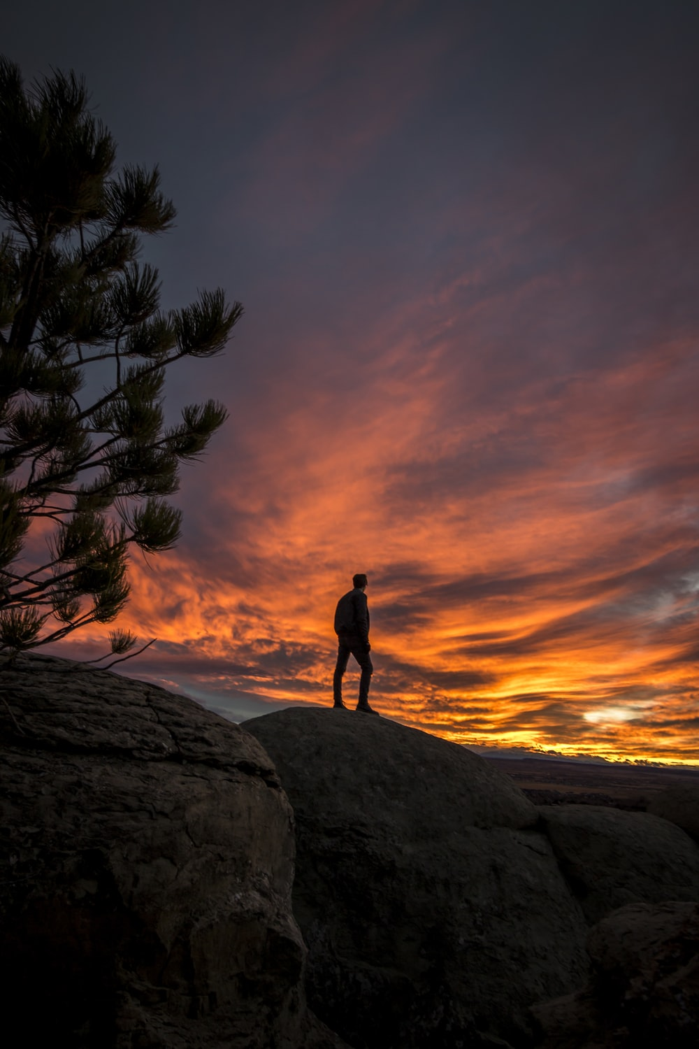 time lapse photography of person standing on cliff silhouette under golden hour