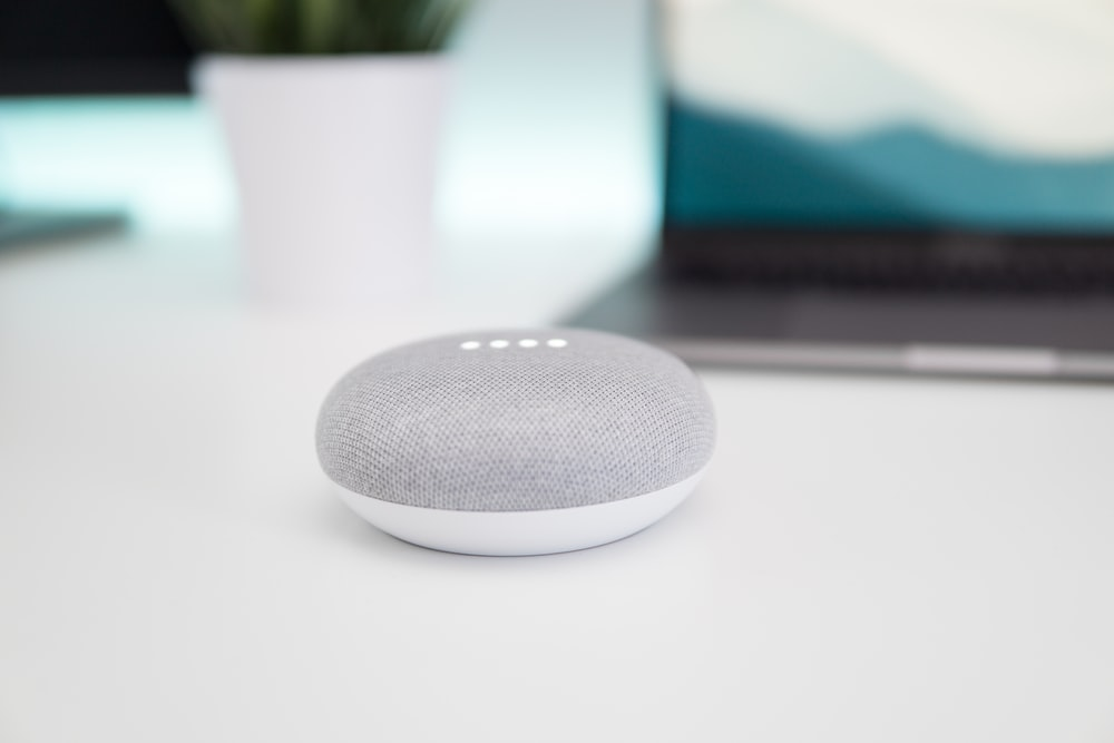 turned on gray and white Google Home Mini speaker on white surface