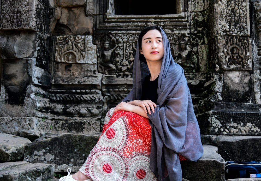 woman sitting on concrete stone