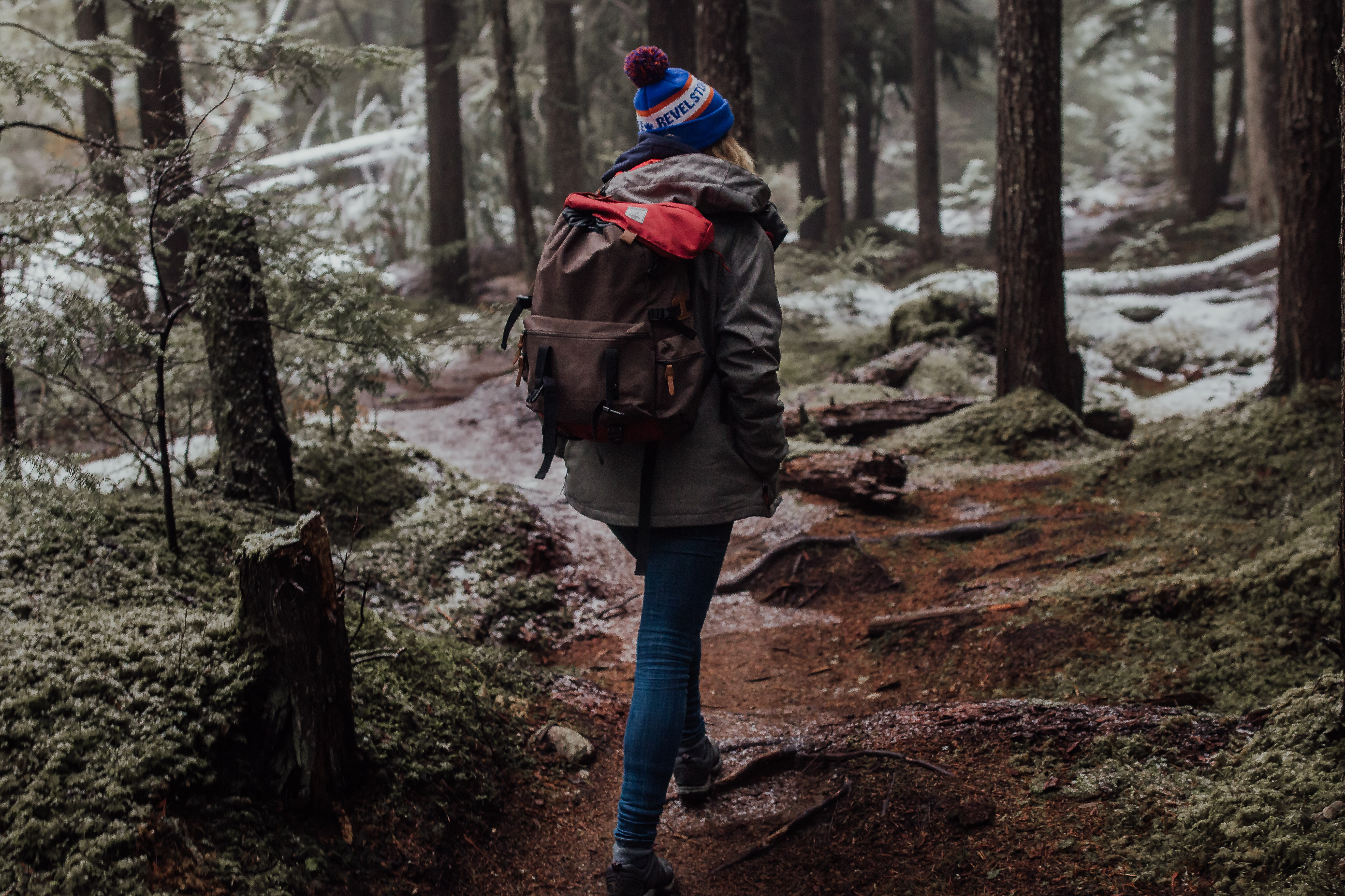 woman with brown backpack walking near the trees