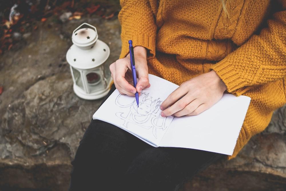 person drawing on sketch book near white lantern