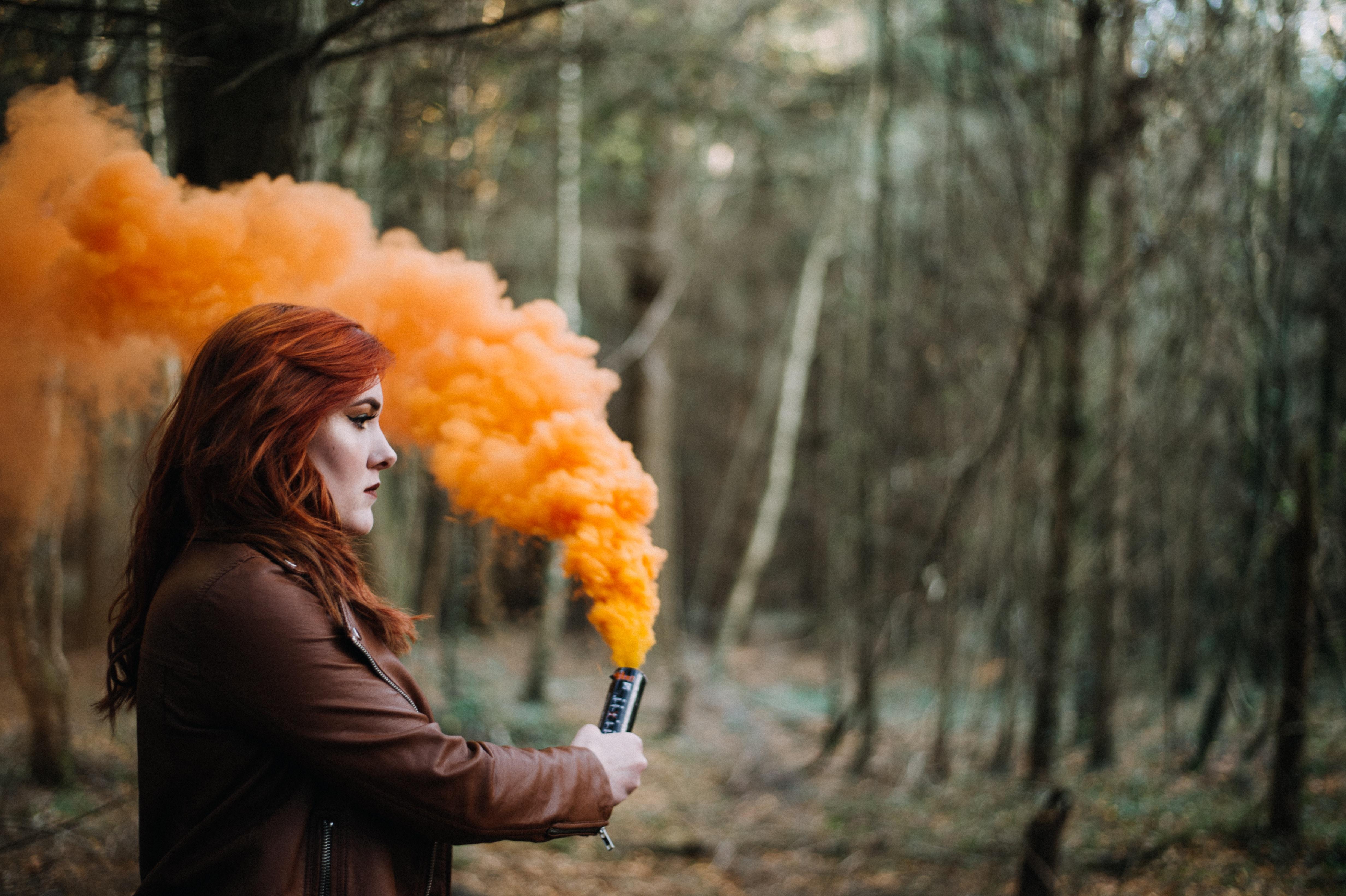 woman holding orange smoke powder surrounded with trees during daytime