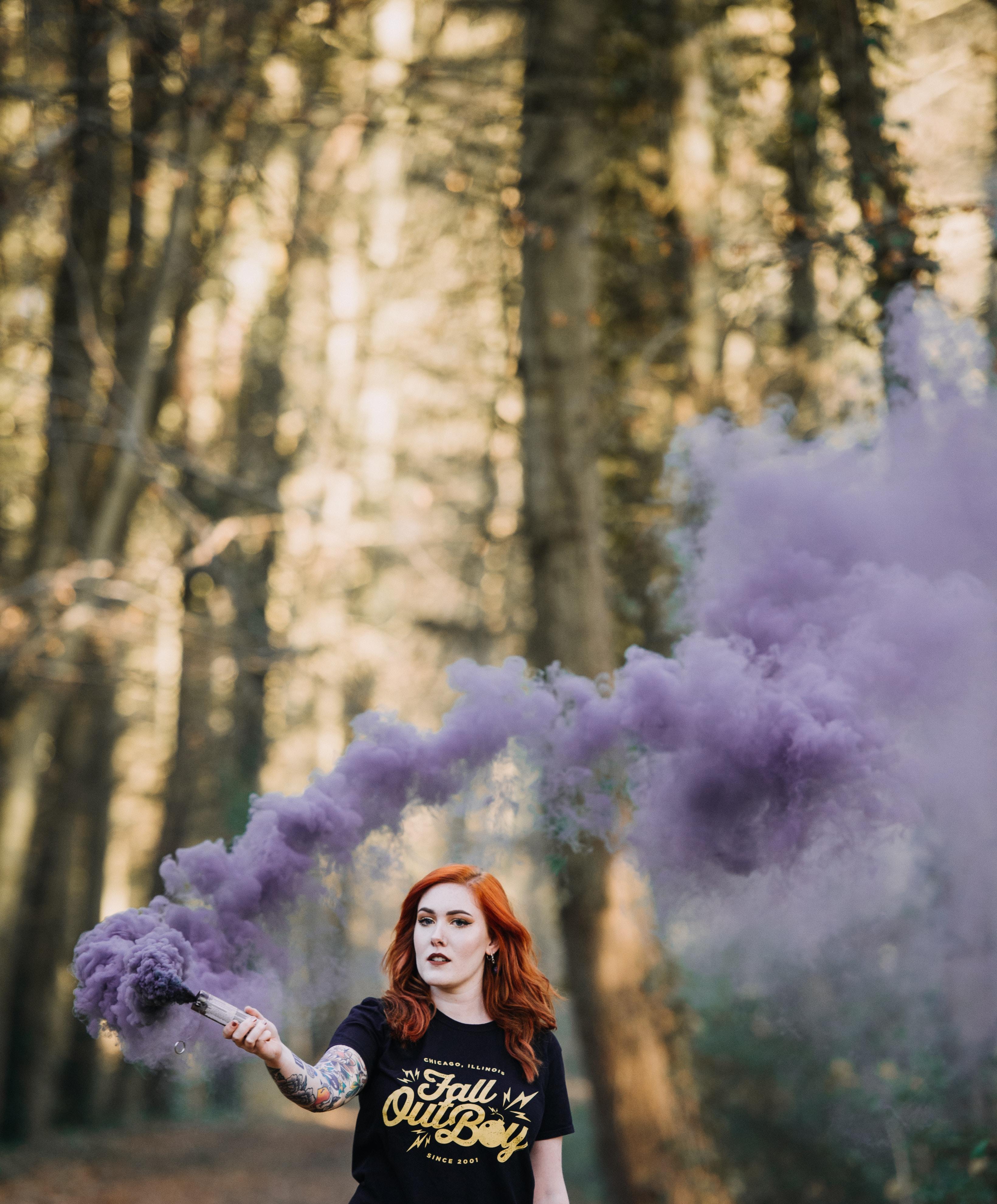 woman holding purple smoke bomb at daytime