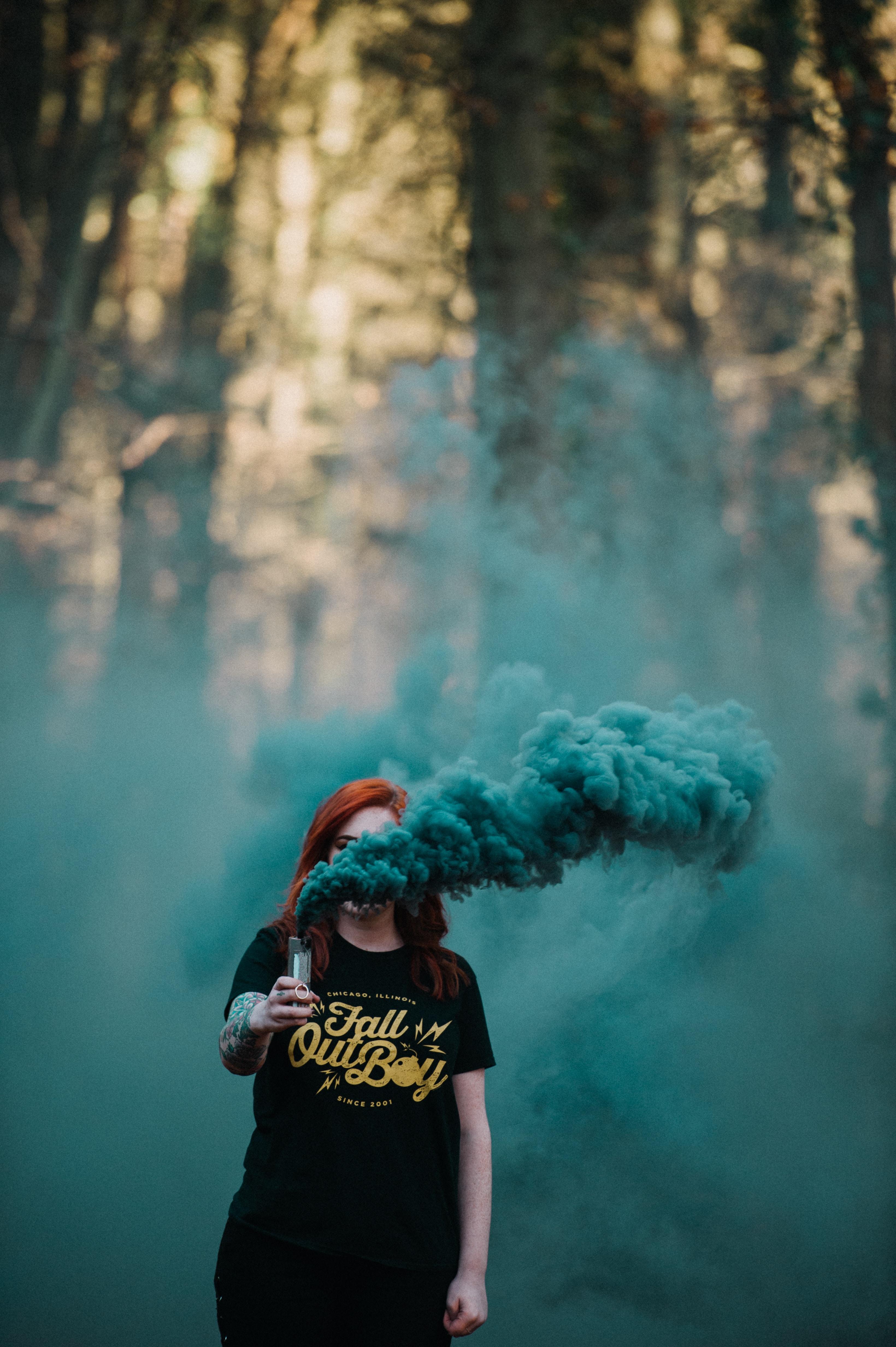 woman holding vaporizer releasing blue smoke near forest