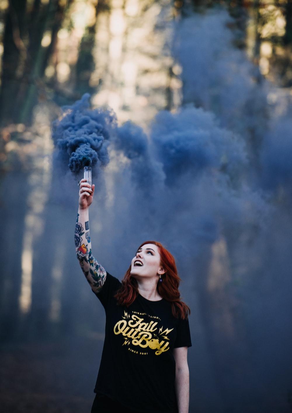 woman holding a blue smoke signal