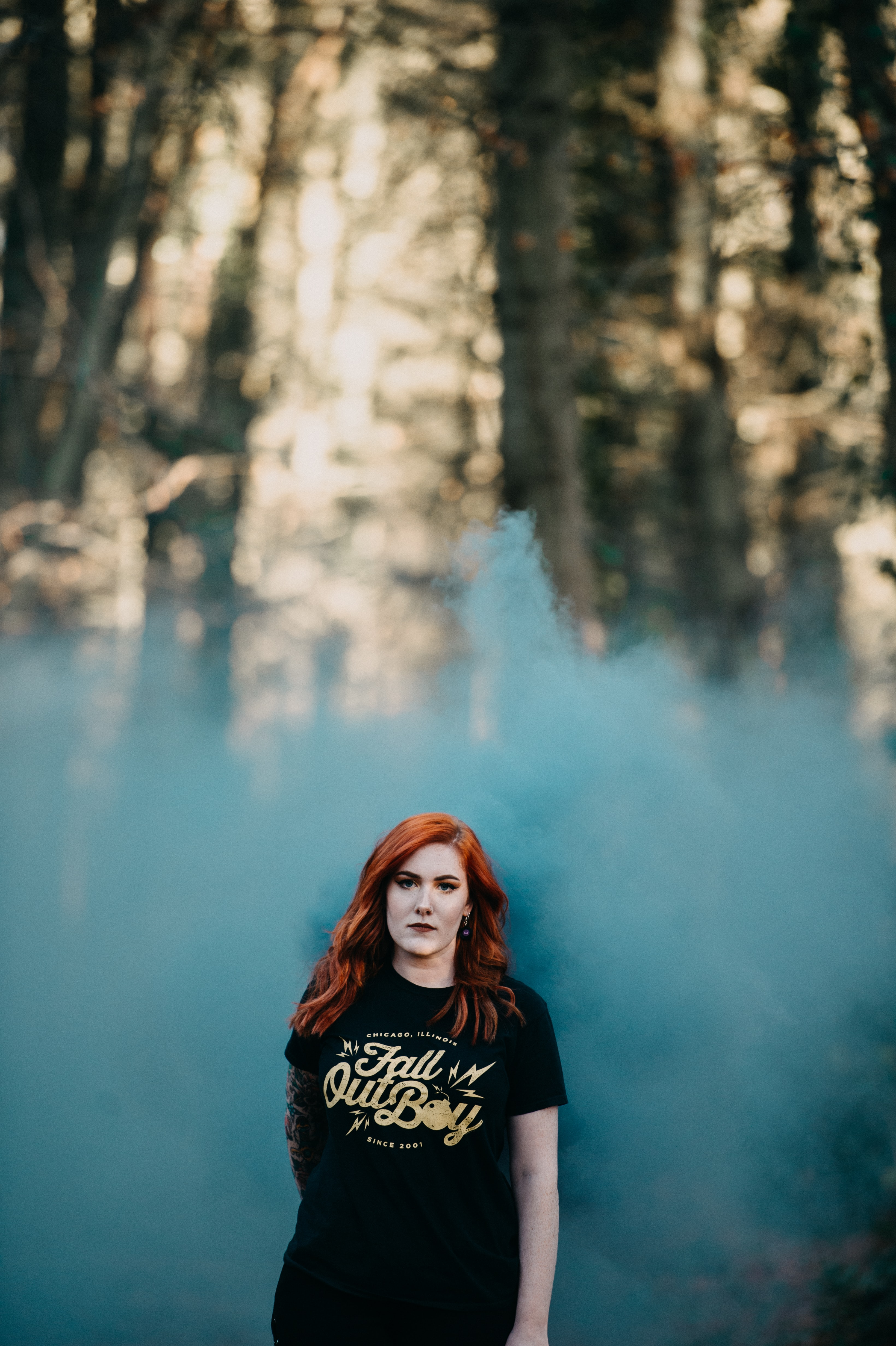 woman in black t-shirt with teal smoke in selective focus photography