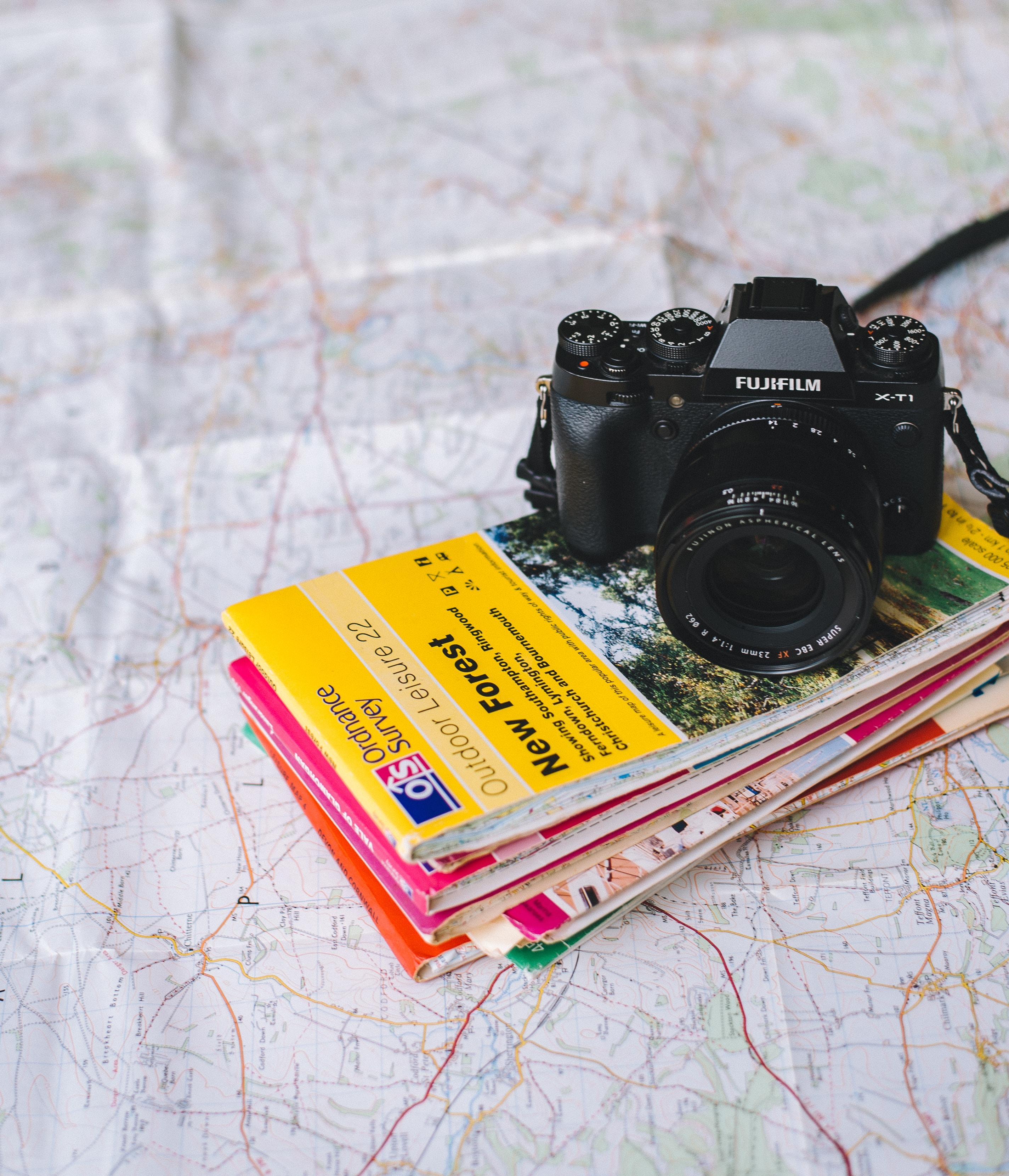 black Fujifilm DSLR camera on books