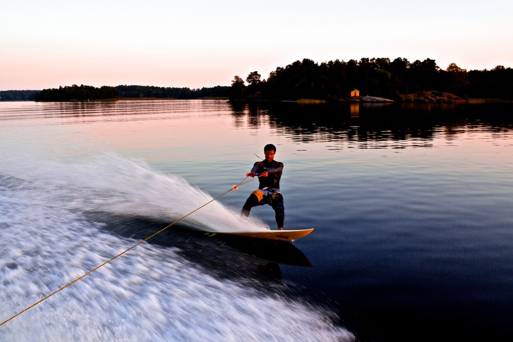 man riding yellow wakeboard on body of water