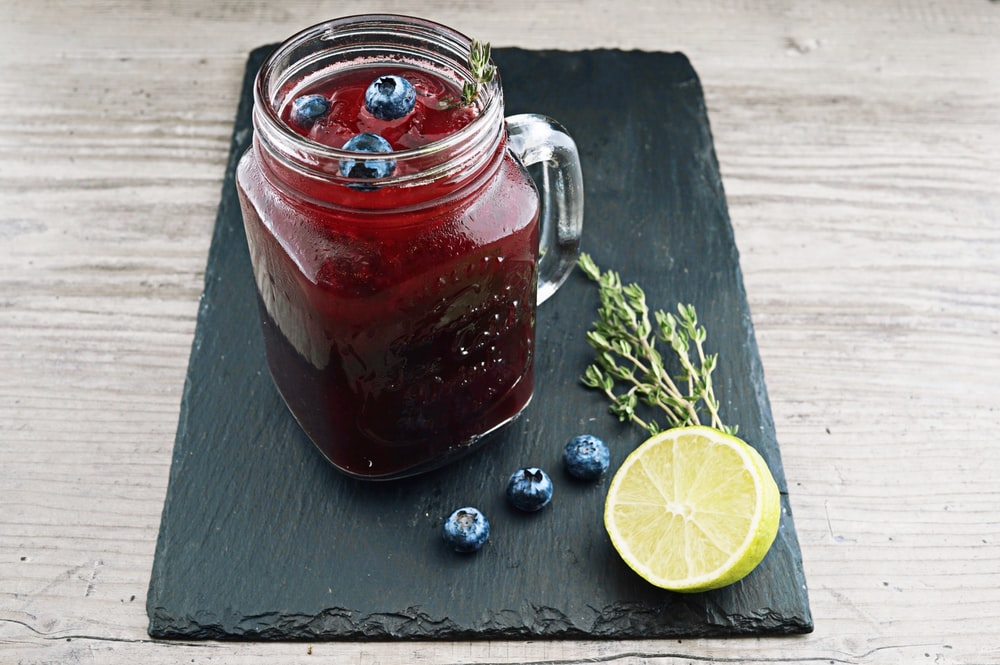 clear glass mason jar with red liquid and lemon beside