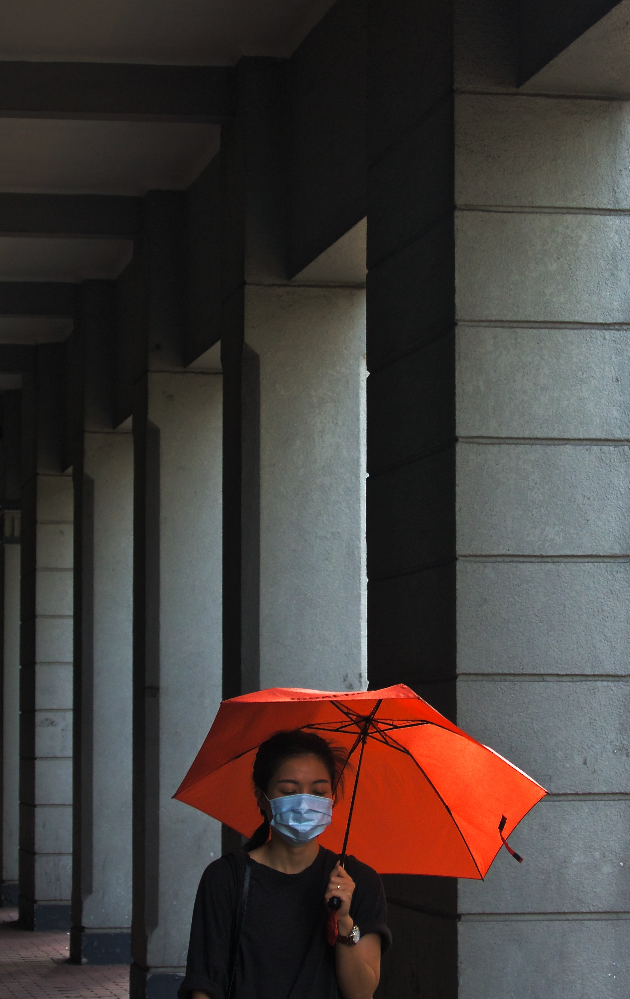 women's holding umbrella beside post