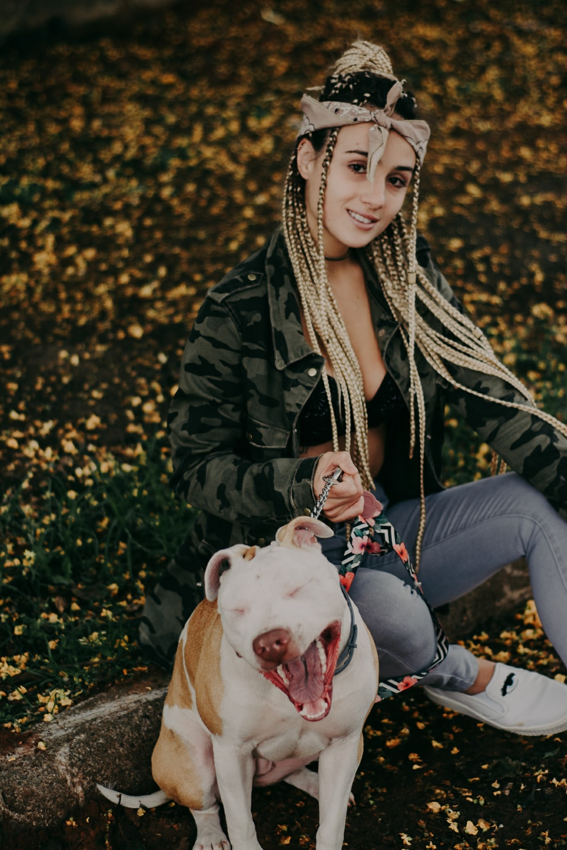 woman sitting beside short-coated dog