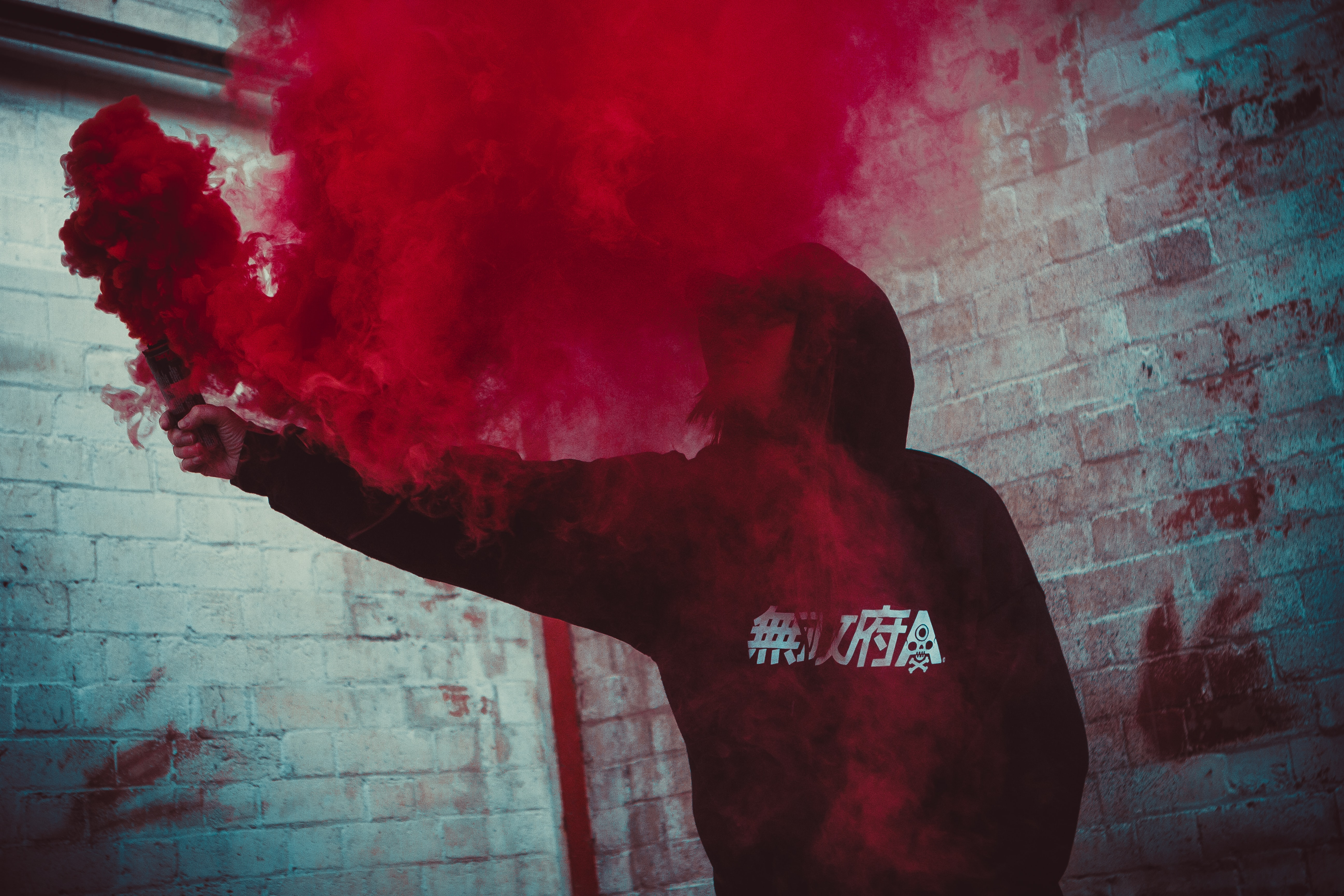 person holding red smoke bonb