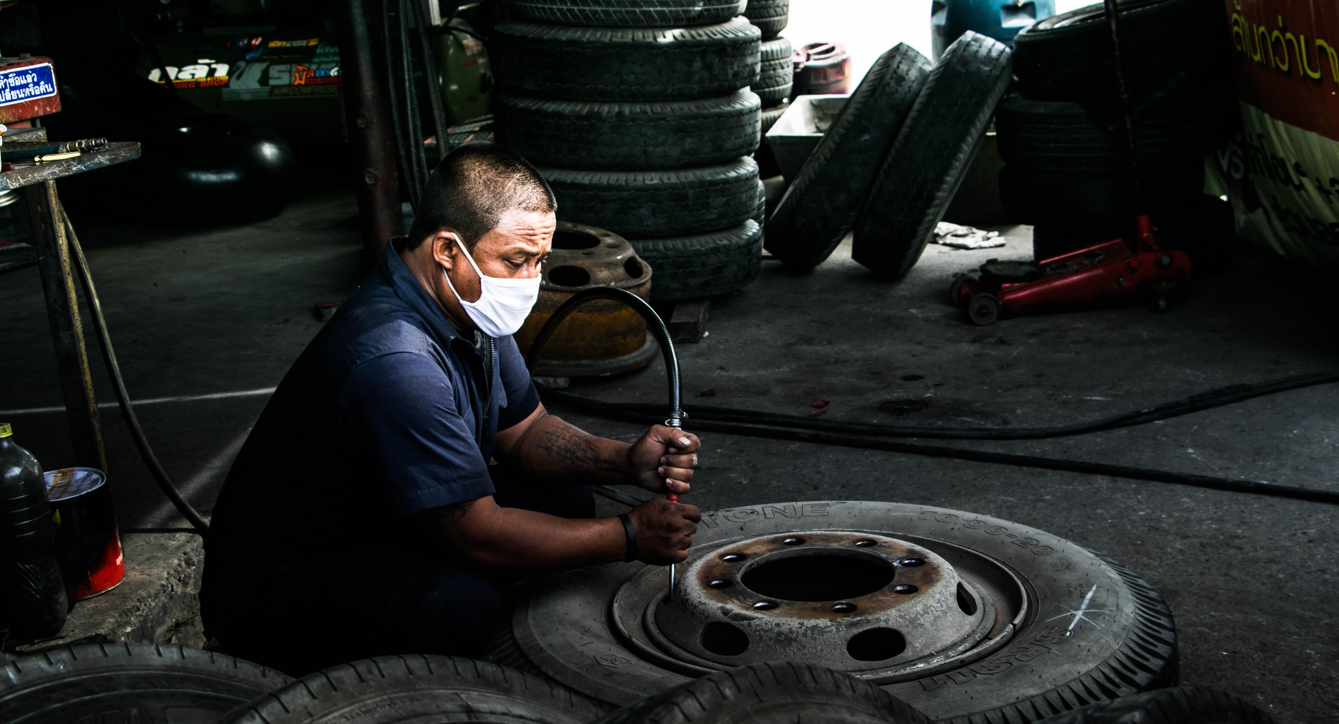 man airing up wheel during daytime