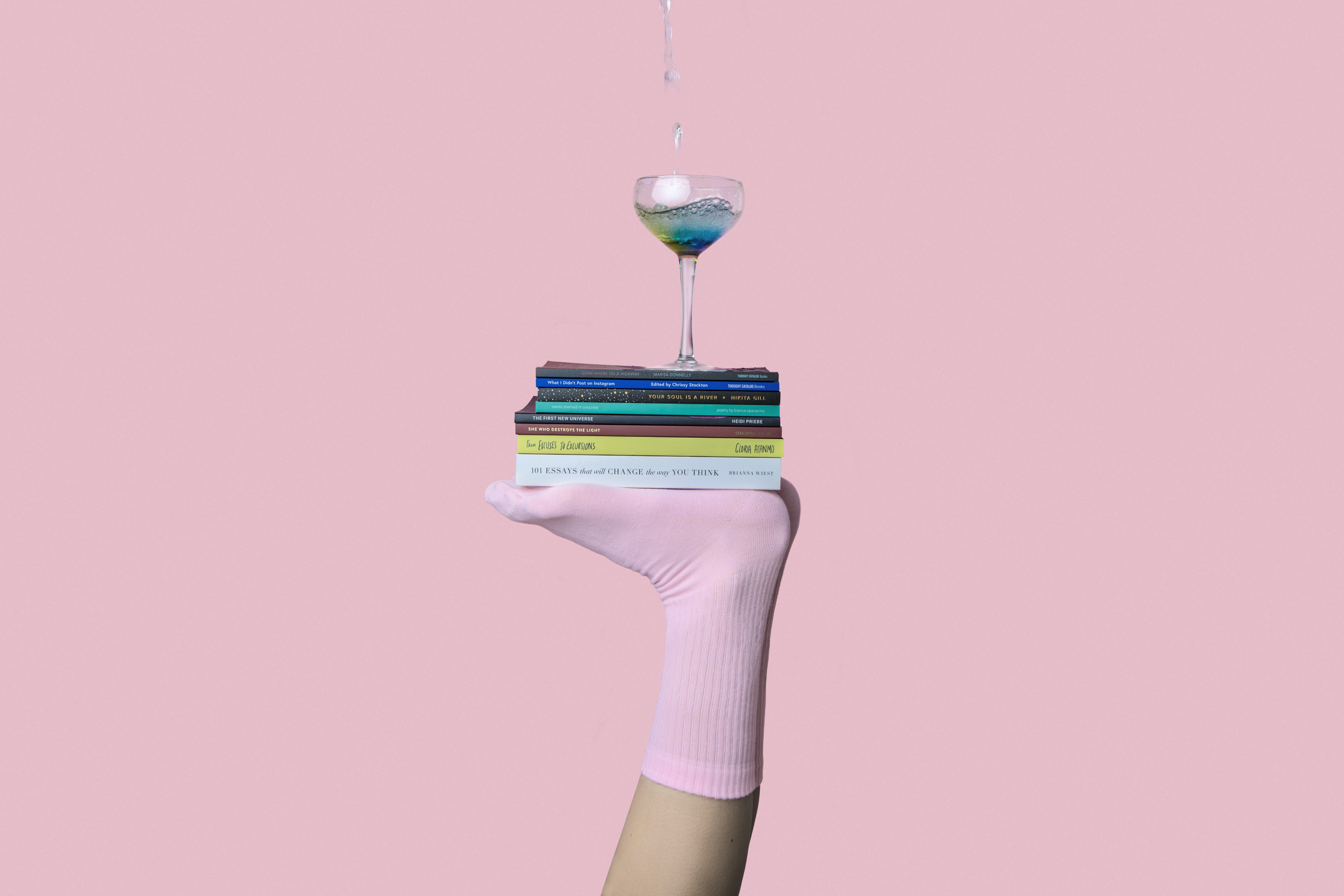 person balancing martini glass above book with feet