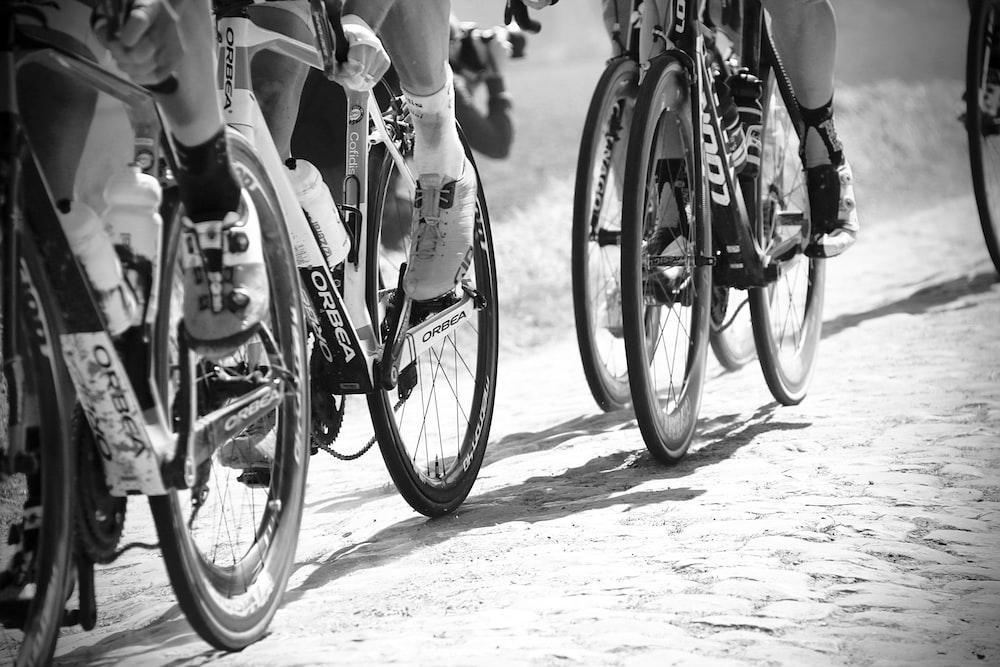 grayscale photo of people racing bikes