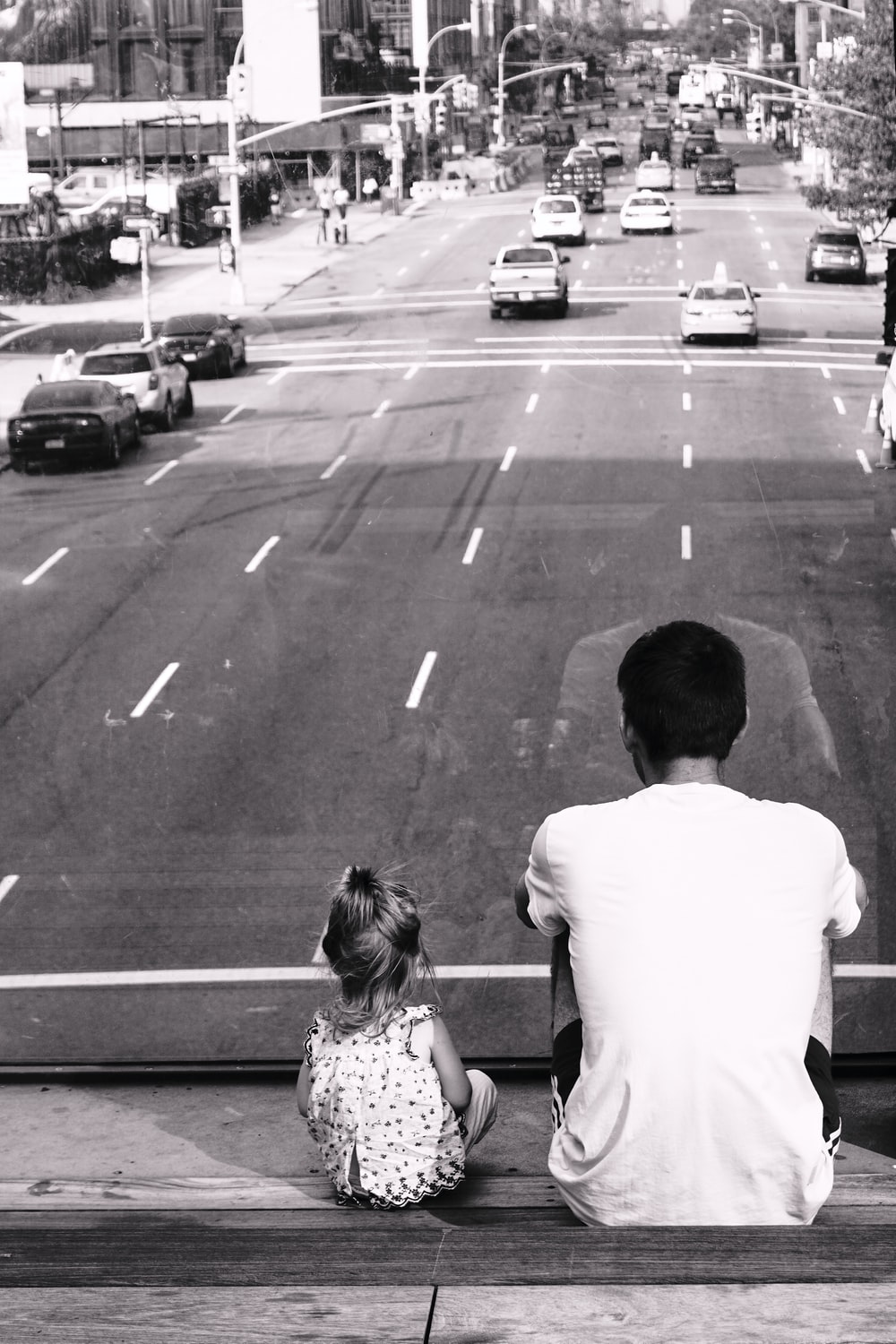 grayscale photography of man and girl sitting on staircase fronting road with passing cars