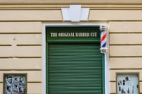 beige building with The Original Barber Cut sign