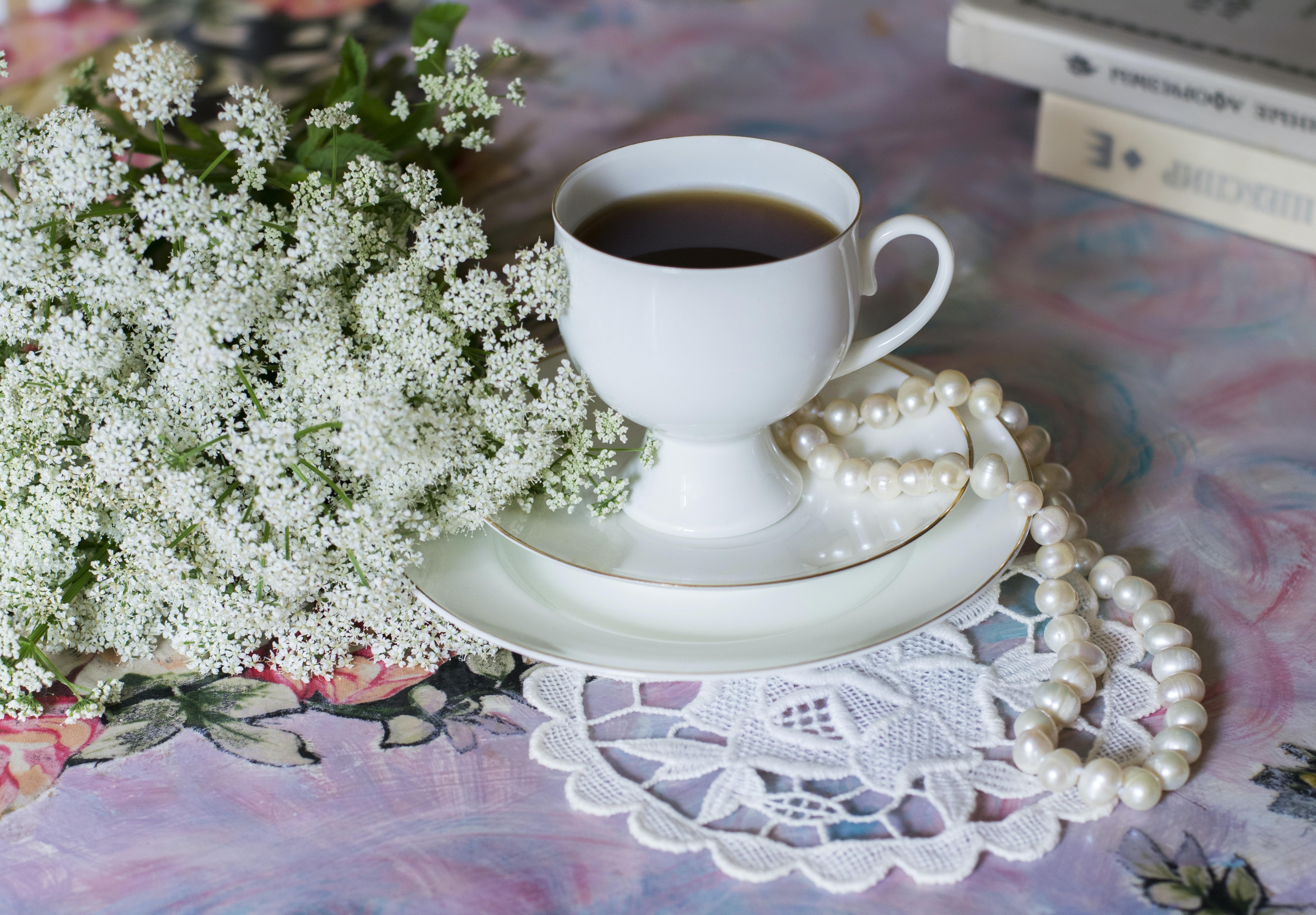 white ceramic cup on ceramic saucer