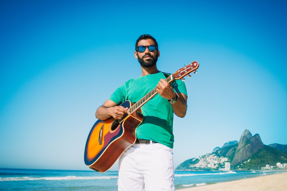 man playing guitar near ocean during daytime