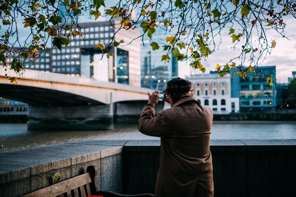 man standing beside river near concrete bridge