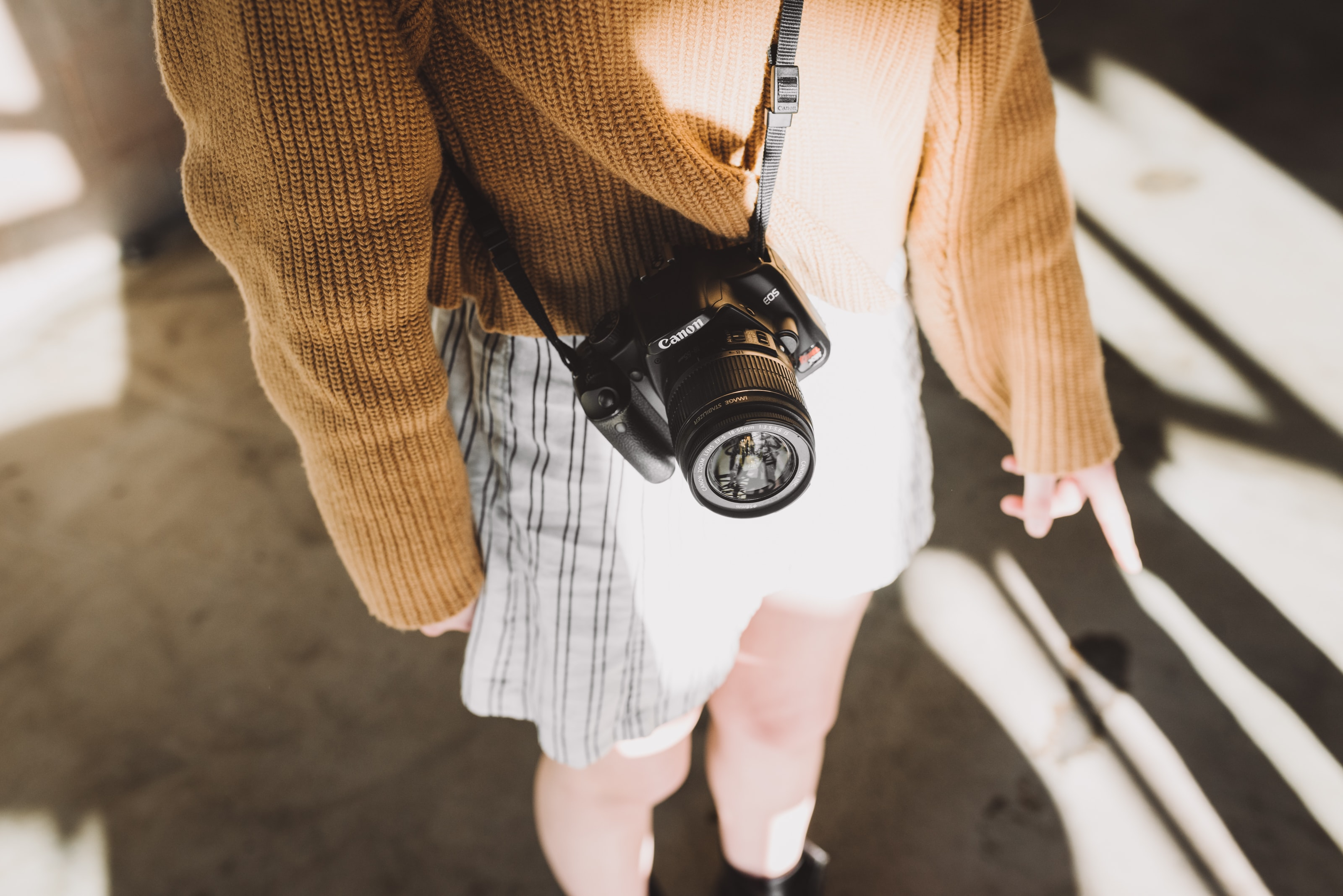 woman wearing brown sweater and white shorts with black Canon DSLR camera sling on her body