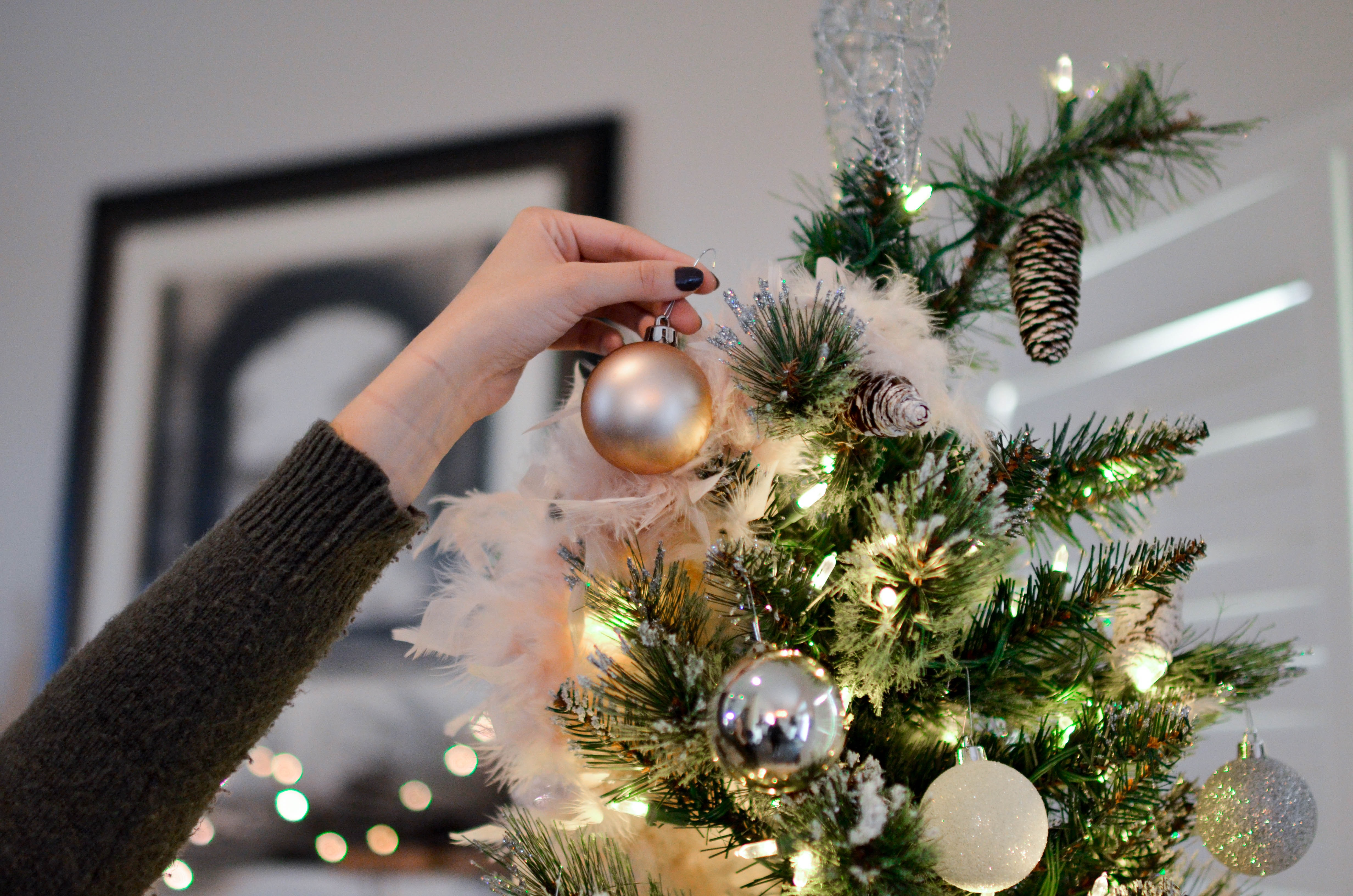 person putting bauble on top of Christmas tree