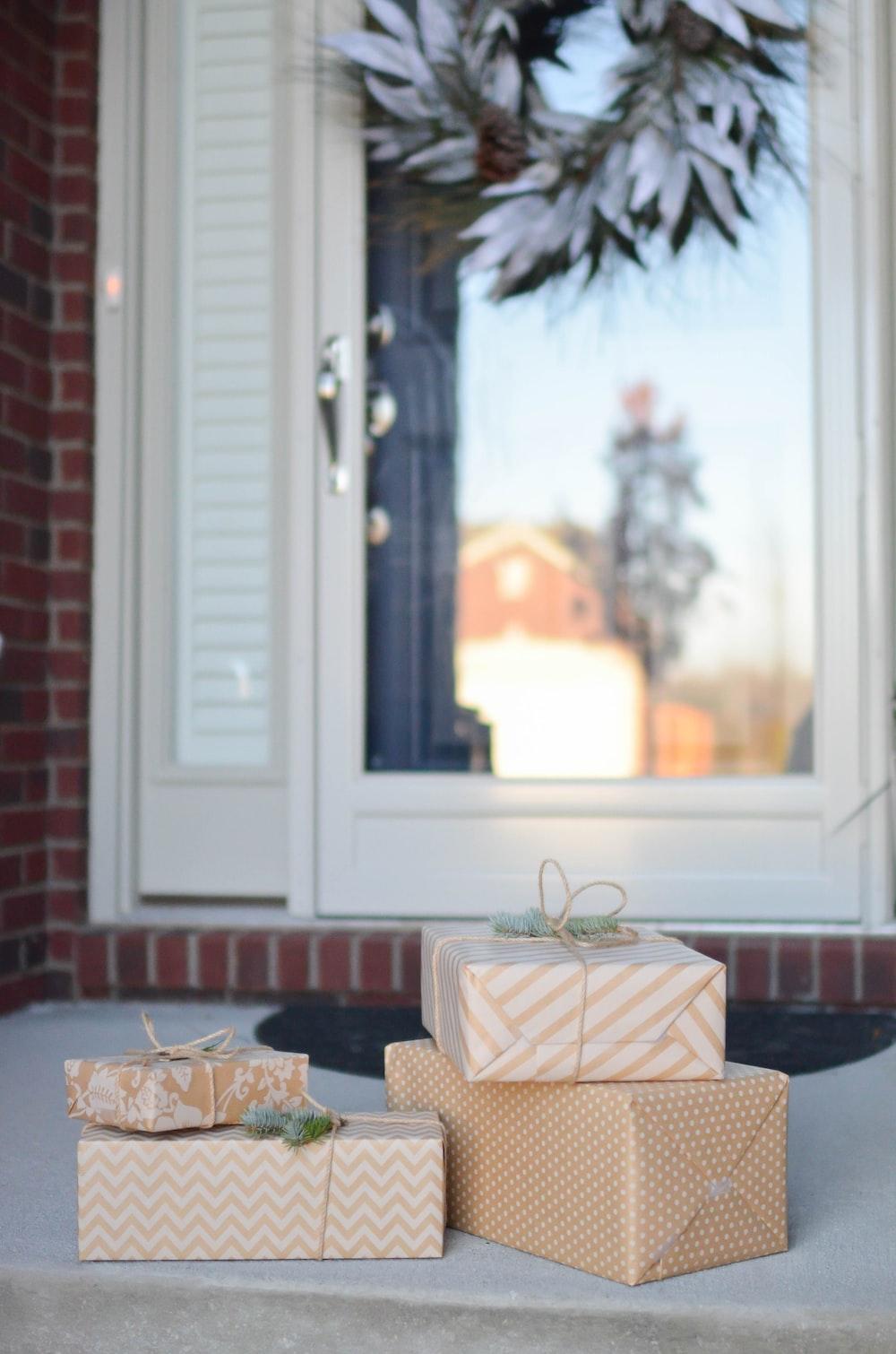 four brown gift boxes near white door