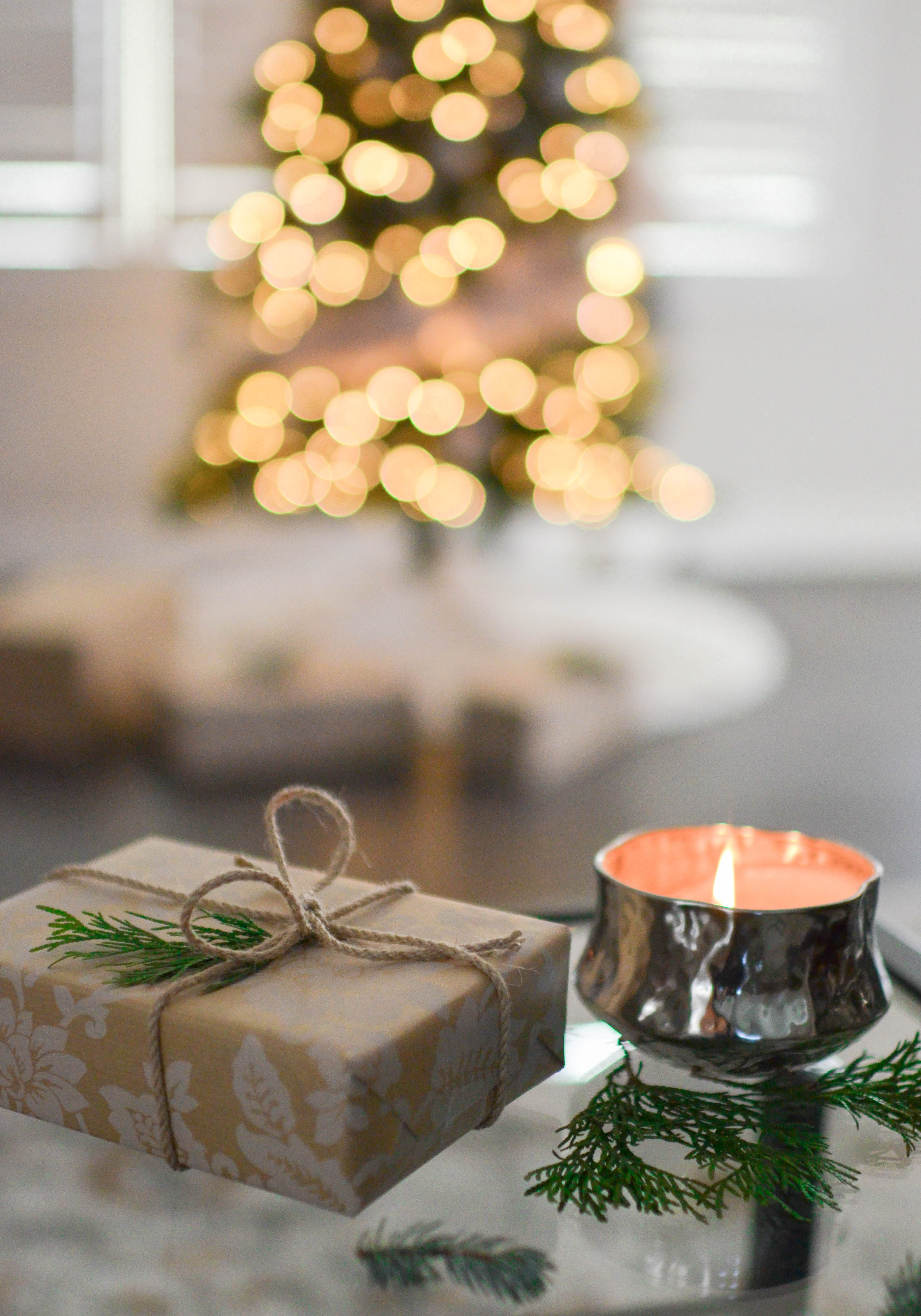brown gift box beside stainless steel votive candle