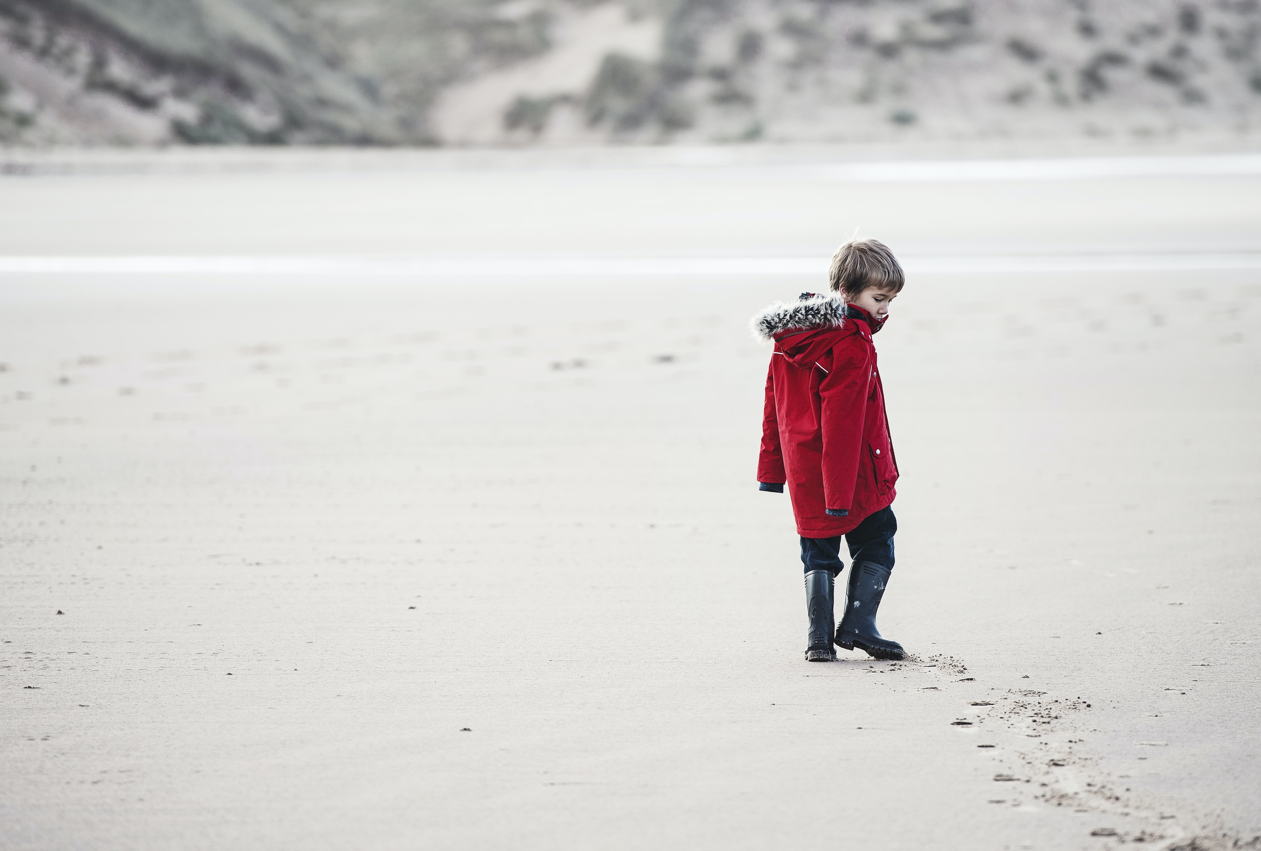 boy walking on sand with tracks
