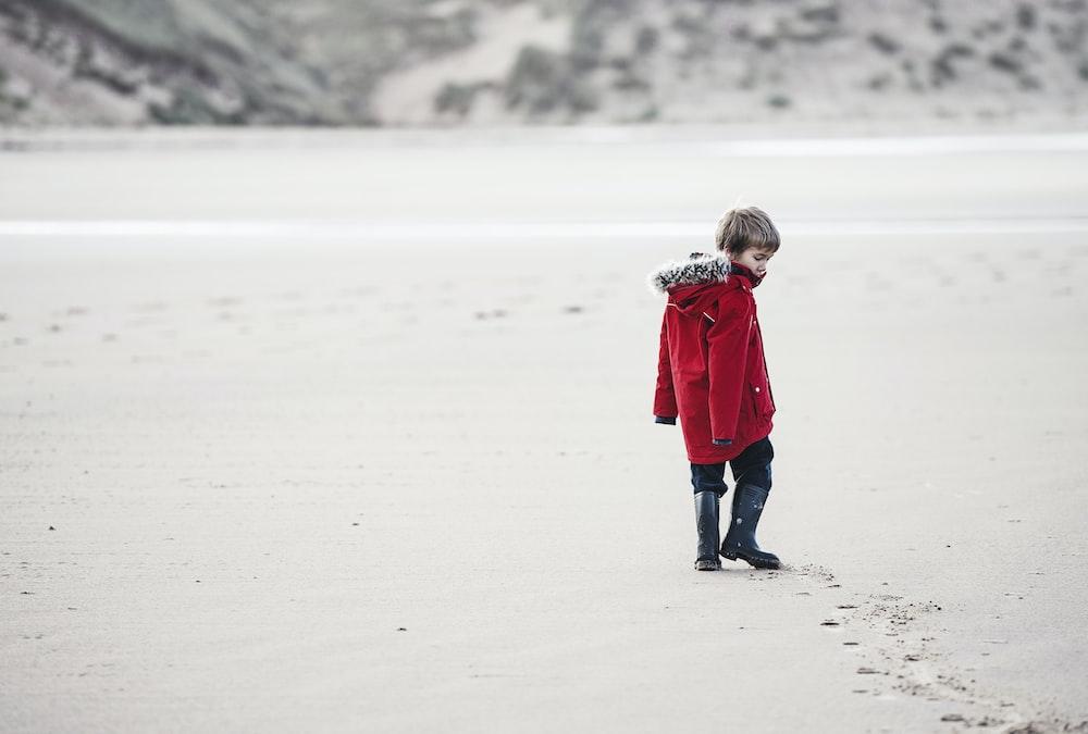 boy walking on sand with tracks