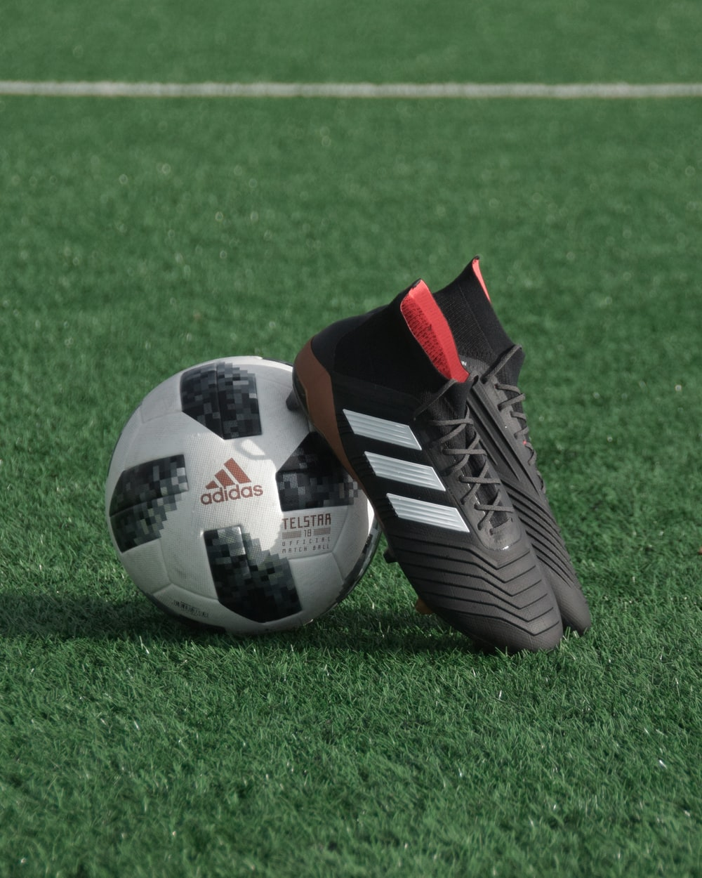 black adidas cleats lean on white and black adidas soccer ball on green grass
