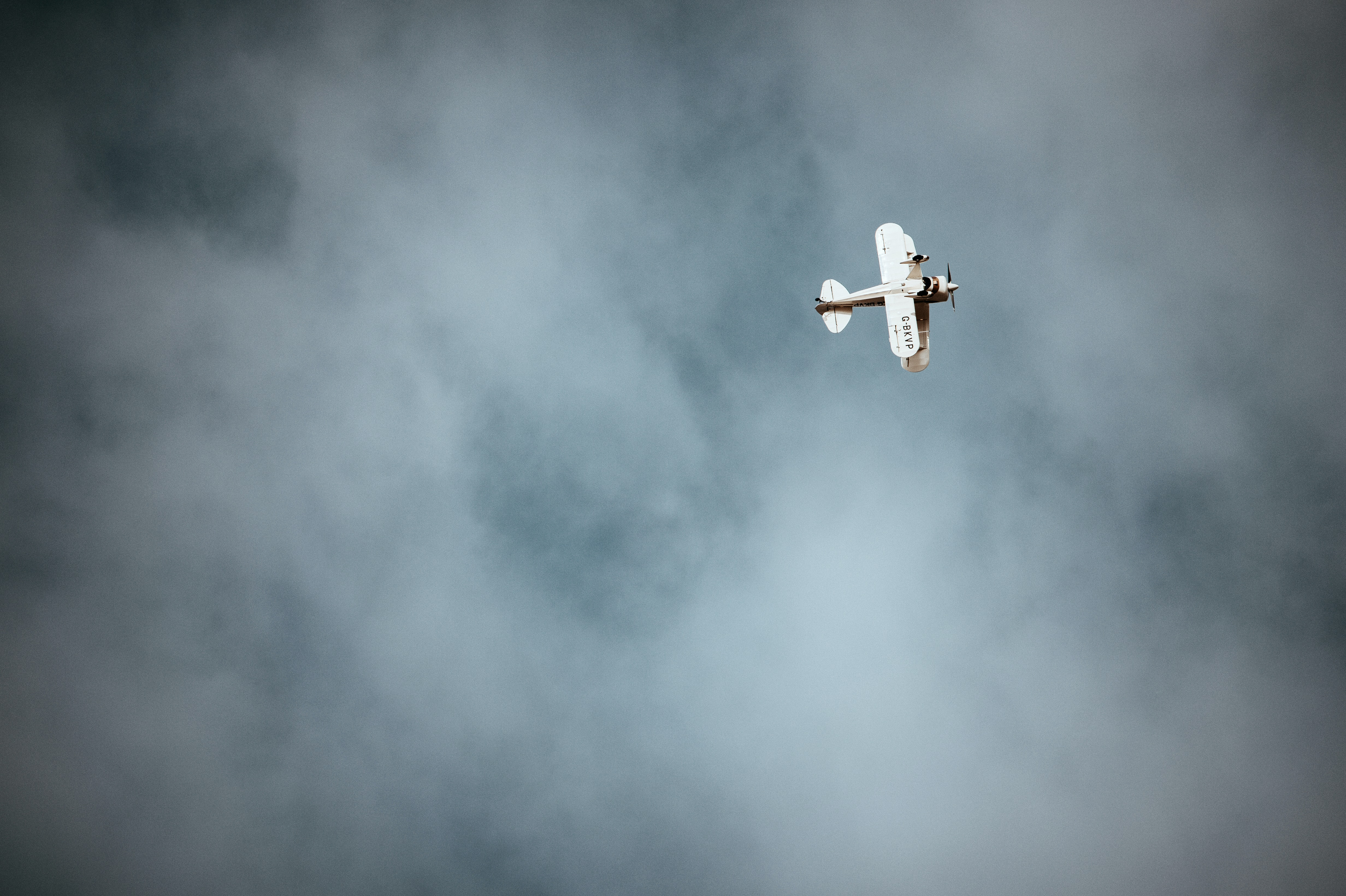 plane flying under white clouds during daytime